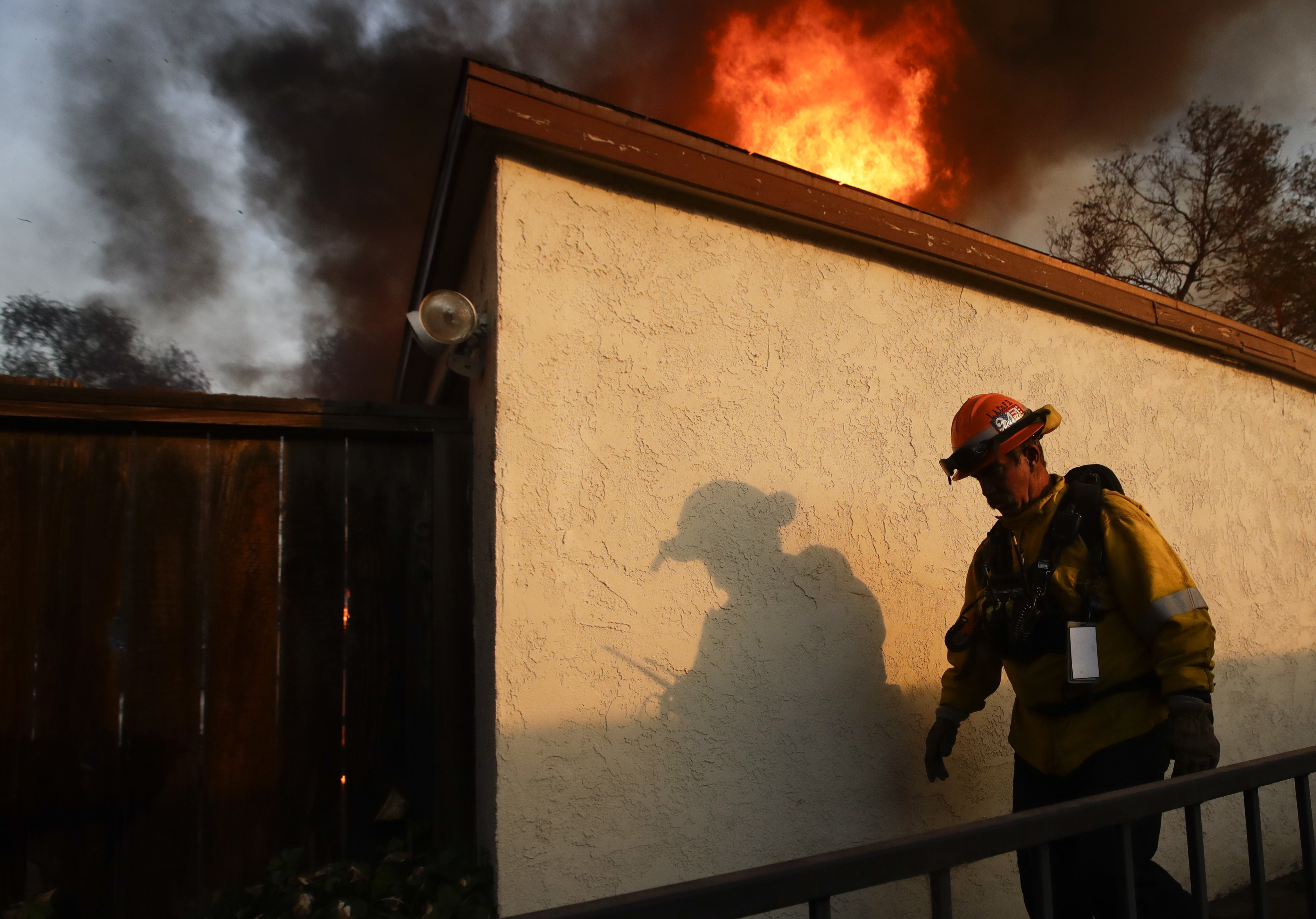 A Los Angeles County firefighter walks past burning house during a wildfire in the Lake View Terrace area of Los Angeles Tuesday, Dec. 5, 2017. Ferocious winds in Southern California have whipped up explosive wildfires, burning a psychiatric hospital and scores of other structures. Tens of thousands of people have been ordered evacuated.  (AP Photo/Chris Carlson)