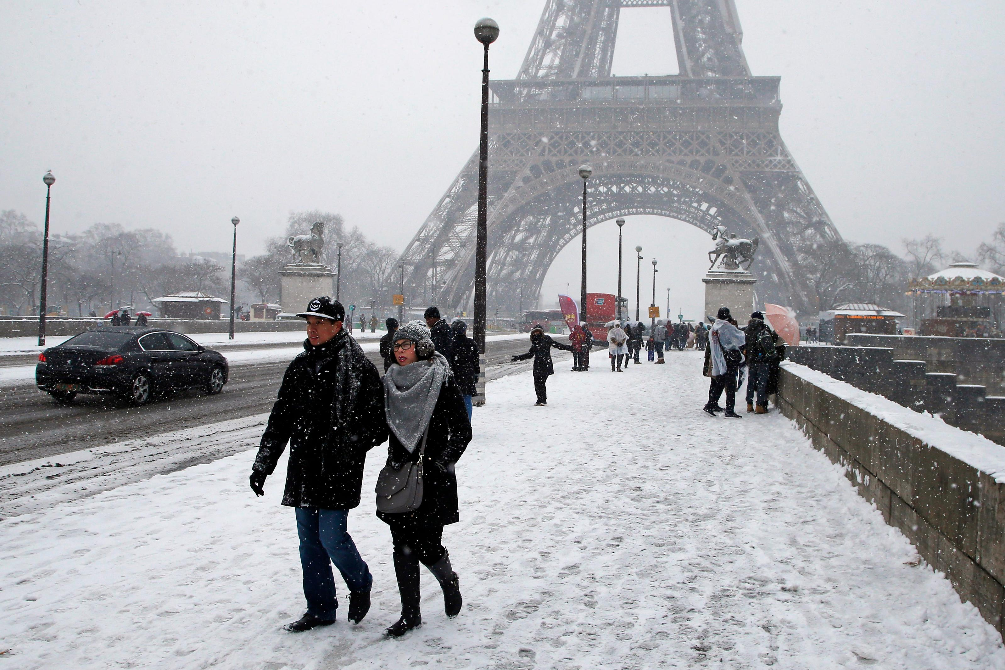 People walk on the snow-covered Iena bridge during a snowfall in Paris, France, Friday, Feb. 9, 2018. The Eiffel Tower is closed and authorities are telling drivers in the Paris region to stay home as snow and freezing rain have hit a swath of France ill-prepared for the wintry weather. (AP Photo/Michel Euler)