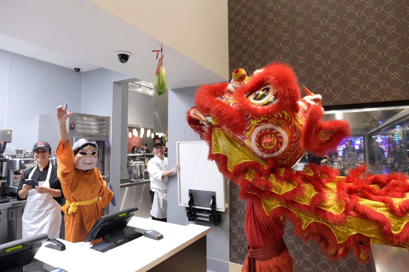 "A lion sniffs at its payment and lettuce during the ""eating the lettuce ceremony (Choy Cheng)"" during the grand opening of the Lucky Dragon Hotel and Casino Saturday, Dec. 3, 2016. (Sam Morris/Las Vegas News Bureau)"