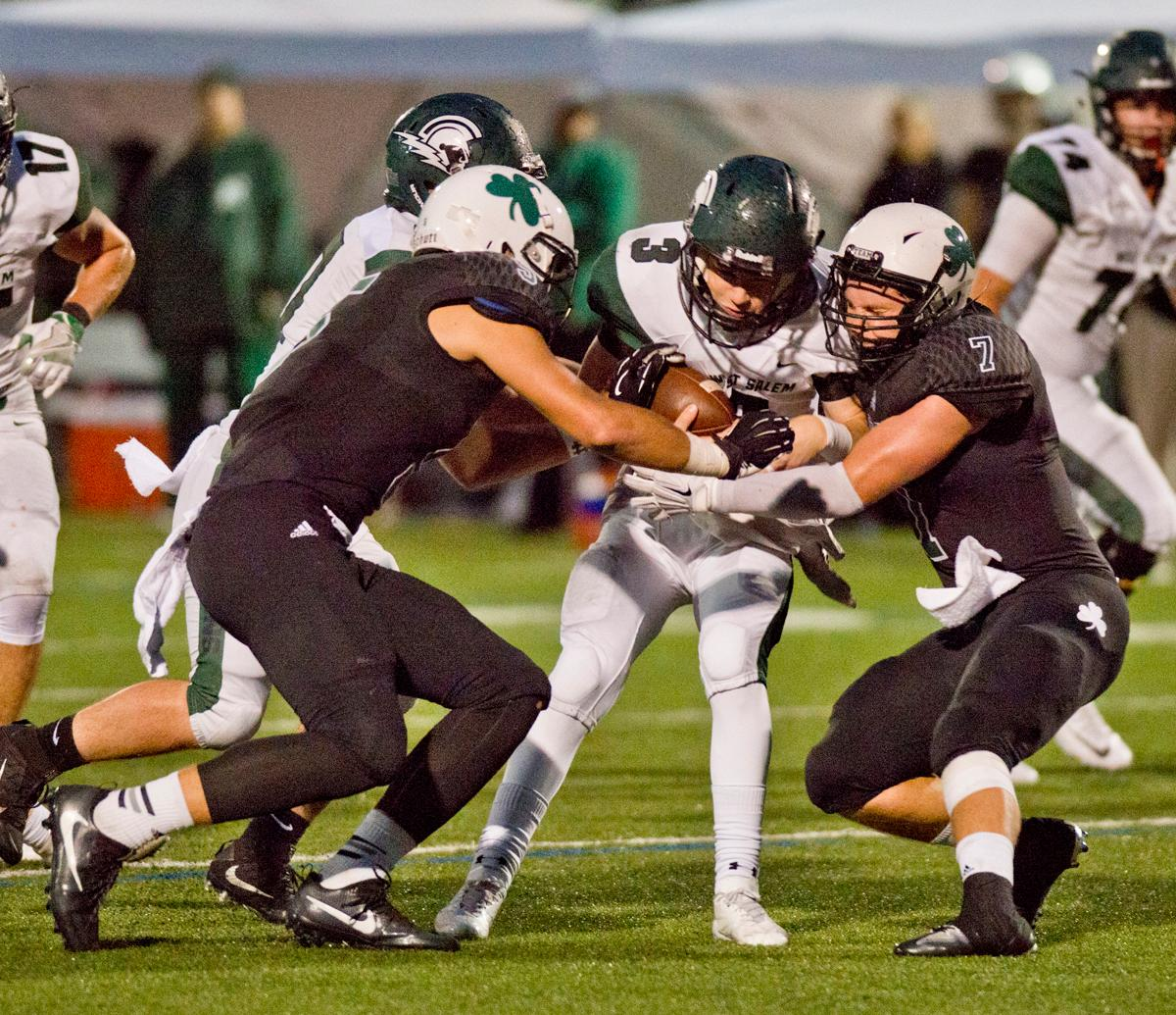 West Salem Titans quarterback Grant Thies (#3) is tackled by Sheldon Irish linebacker Jaren Banks (#7). On a rainy Monday evening Sheldon defeated West Salem 41-7. The game had been postponed from Friday due to unhealthy levels of smoke in the atmosphere due to nearby forest fires. Photo by Dan Morrison, Oregon News Lab