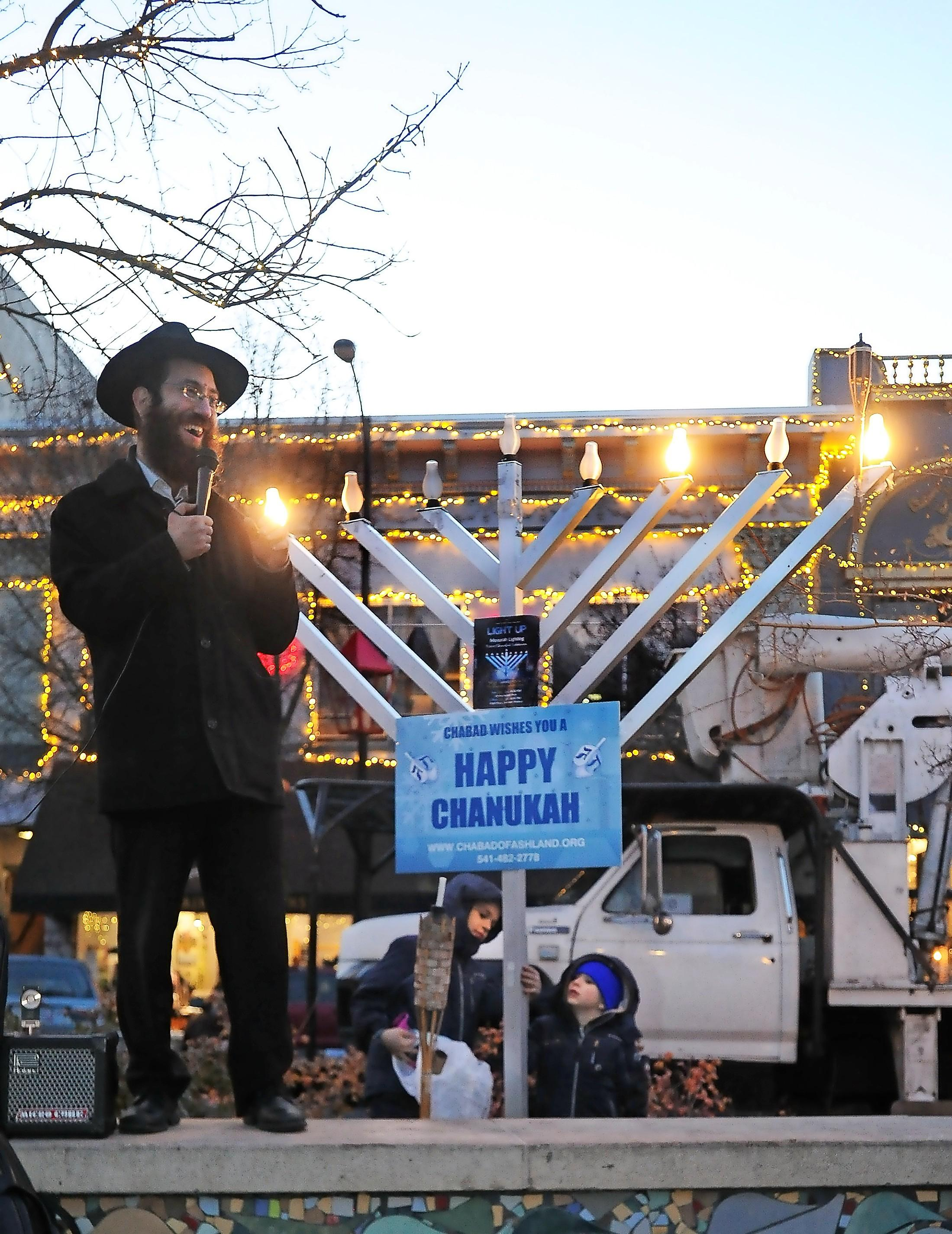 Rabbi Avi Zwiebel smiles as two boys play with the switch to the menorah lights Sunday on the Ashland Plaza. Photo by Denise Baratta