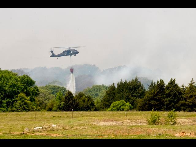A UH-60 Black Hawk helicopter assists local firefighters near Guthrie, Okla., May 5, 2014, as they attempt to contain wildfires that claimed more than 6,000 acres of land and numerous homes in less than 24 hours.