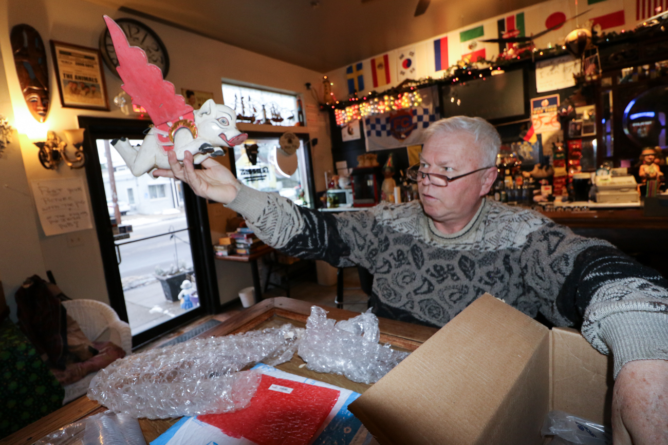 John Cody, co-owner, was born in London. He is seen here unboxing a handmade flying pig he purchased from overseas. / Image: Ronny Salerno // Published: 2.4.19