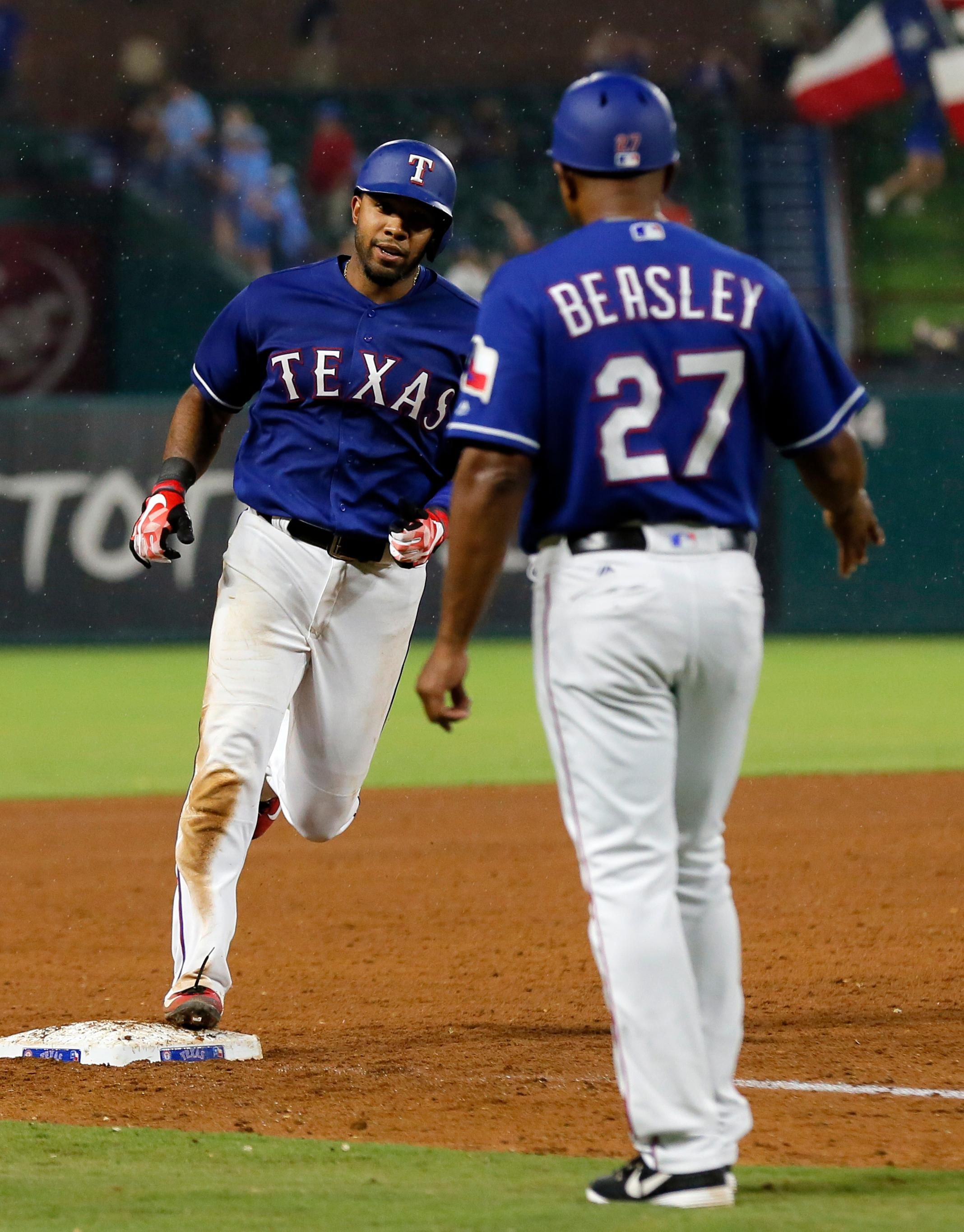 Texas Rangers' Elvis Andrus, left, rounds third past third base coach Tony Beasley (27) after hitting a two-run home run during the sixth inning of a baseball game against the Seattle Mariners on Wednesday, Aug. 2, 2017, in Arlington, Texas. (AP Photo/Tony Gutierrez)