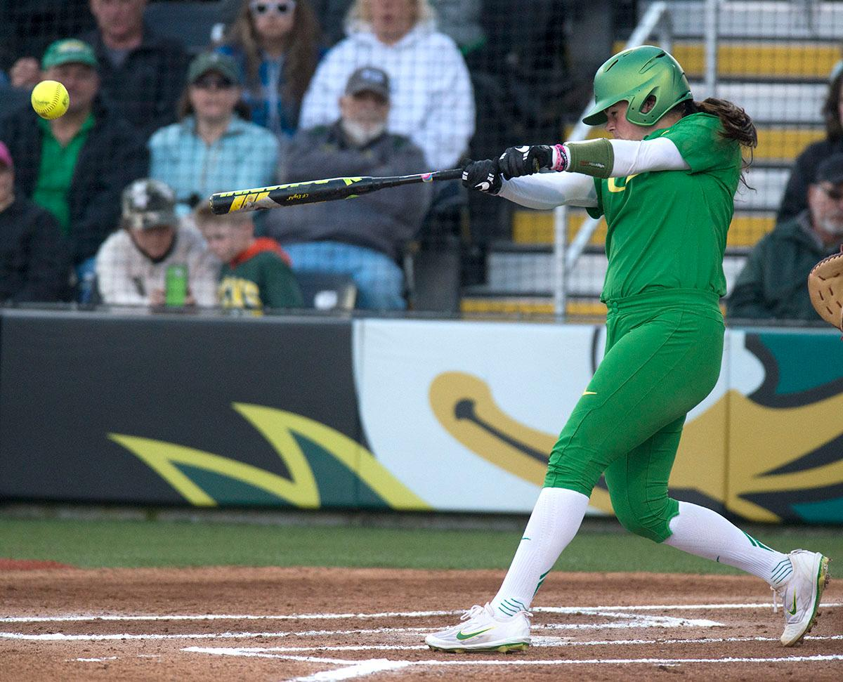 Oregon Ducks catcher Gwen Svekis (#21) hits the ball. The No. 5 Oregon Ducks defeated the No. 2 Florida State Seminoles in both games of the doubleheader (11-0, 3-1) on Saturday afternoon. This sweep of the first two rounds of the postseason happened in front of a soldout crowd of 2,517 at Jane Sanders Stadium. Photo by Cheyenne Thorpe, Oregon News Lab