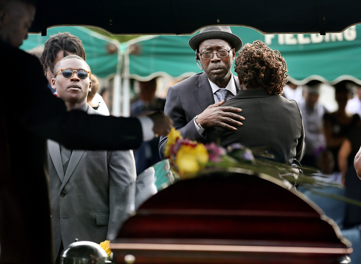 Parents of Tywanza Sanders, Tyrone Sanders and Felicia Sanders comfort each other at the graveside of their son Saturday, June 27, 2015, at Emanuel AME Cemetery in Charleston, S.C. According to a pamphlet given at the funeral, Sanders died trying to protect Susie Jackson, his aunt, and Felicia Sanders, his mother who survived the shooting. Sanders' last words were to the shooter, who killed nine people at the church June 17, the pamphlet said. (Grace Beahm/The Post And Courier via AP)