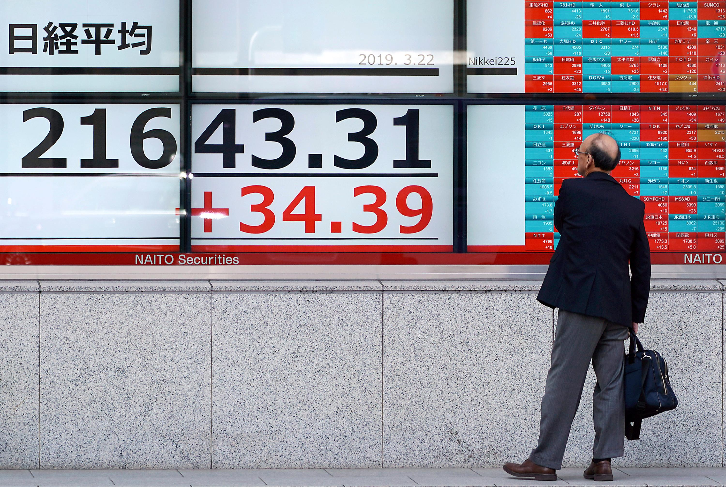 A man looks at an electronic stock board showing Japan's Nikkei 225 index at a securities firm in Tokyo Friday, March 22, 2019.{ } (AP Photo/Eugene Hoshiko)