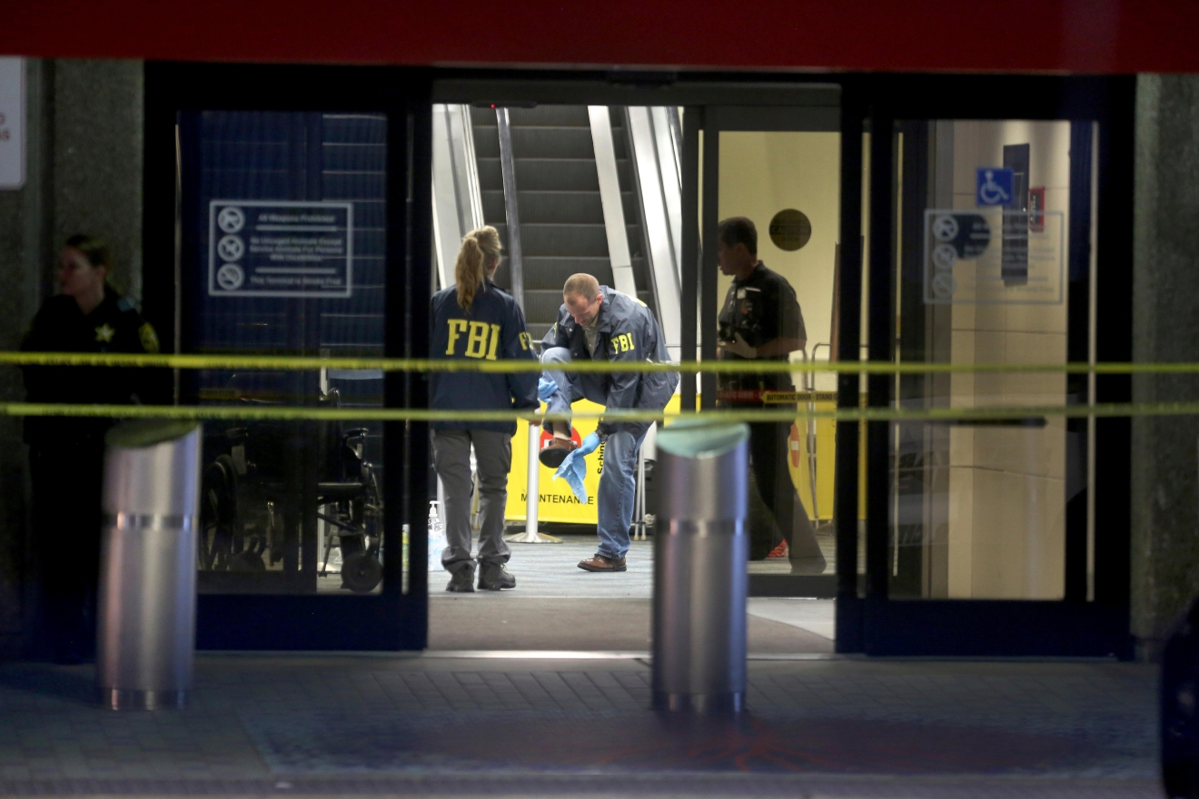 An FBI agent wipes off his shoe while working the crime scene in Terminal 2 at Ft. Lauderdale-Hollywood International Airport, Saturday, Jan. 7, 2017,  the day after a shooting in the baggage area.  Authorities say Army veteran Esteban Santiago of Anchorage, Alaska, drew a gun from his checked luggage on arrival and opened fire on fellow travelers.   (Mike Stocker/South Florida Sun-Sentinel via AP)