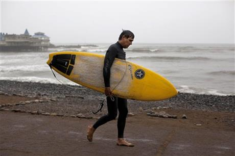 A man walks with his surfboard after a morning of surfing in the Pacific Ocean waters of Makaha beach, in Lima, Peru, Wednesday, April 2, 2014.