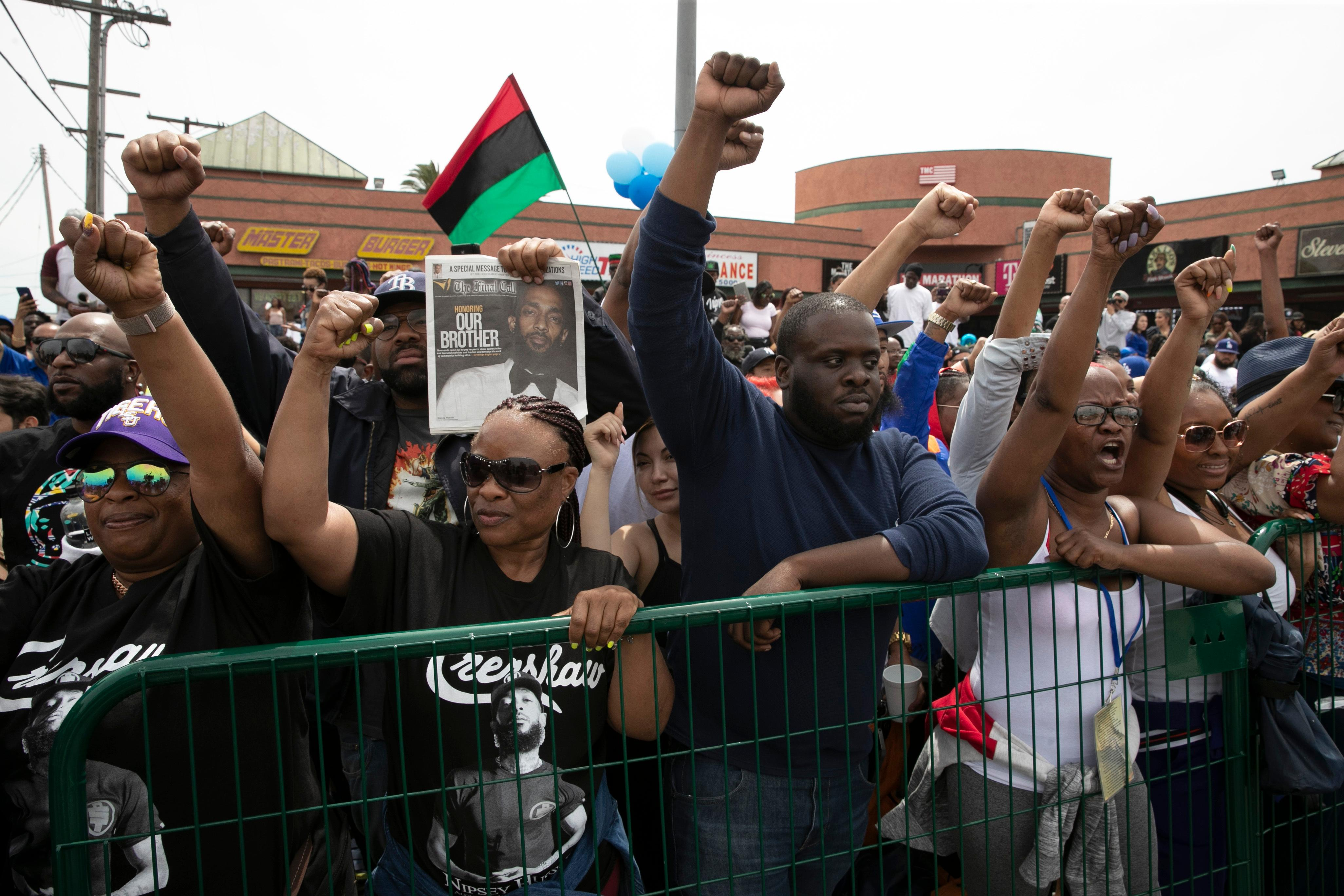 People hold up their fists while waiting for a hearse carrying the casket of slain rapper Nipsey Hussle to pass by in front of Hussle's clothing store The Marathon Thursday, April 11, 2019, in Los Angeles.{ } (AP Photo/Jae C. Hong)