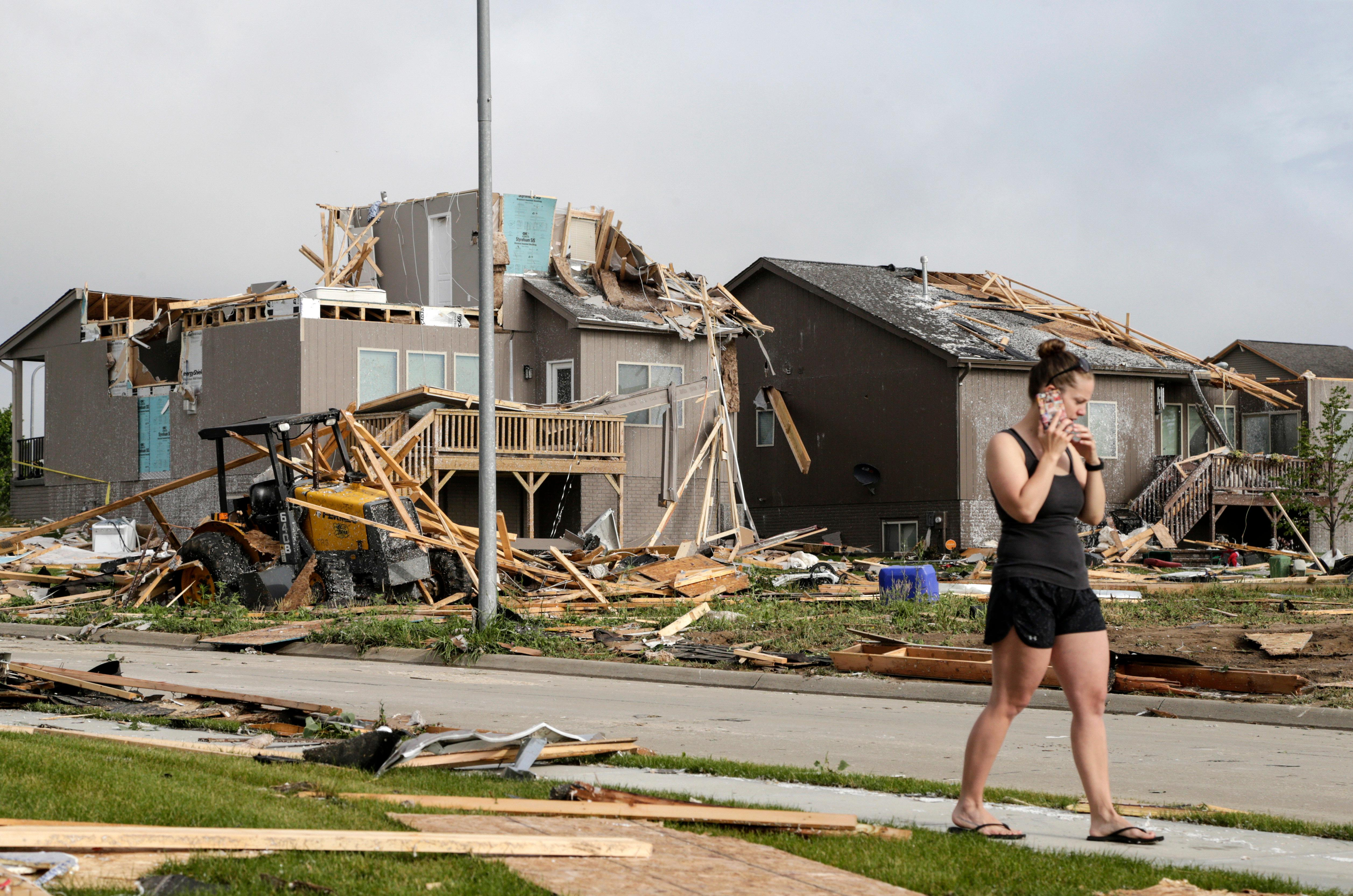A neighbor whose home was damaged by a storm talks on the phone in front of a row of damaged homes in the Hyda Hills neighborhood in Bellevue, Neb., Saturday, June 17, 2017. A severe weather front passed through the area the previous evening. (AP Photo/Nati Harnik)