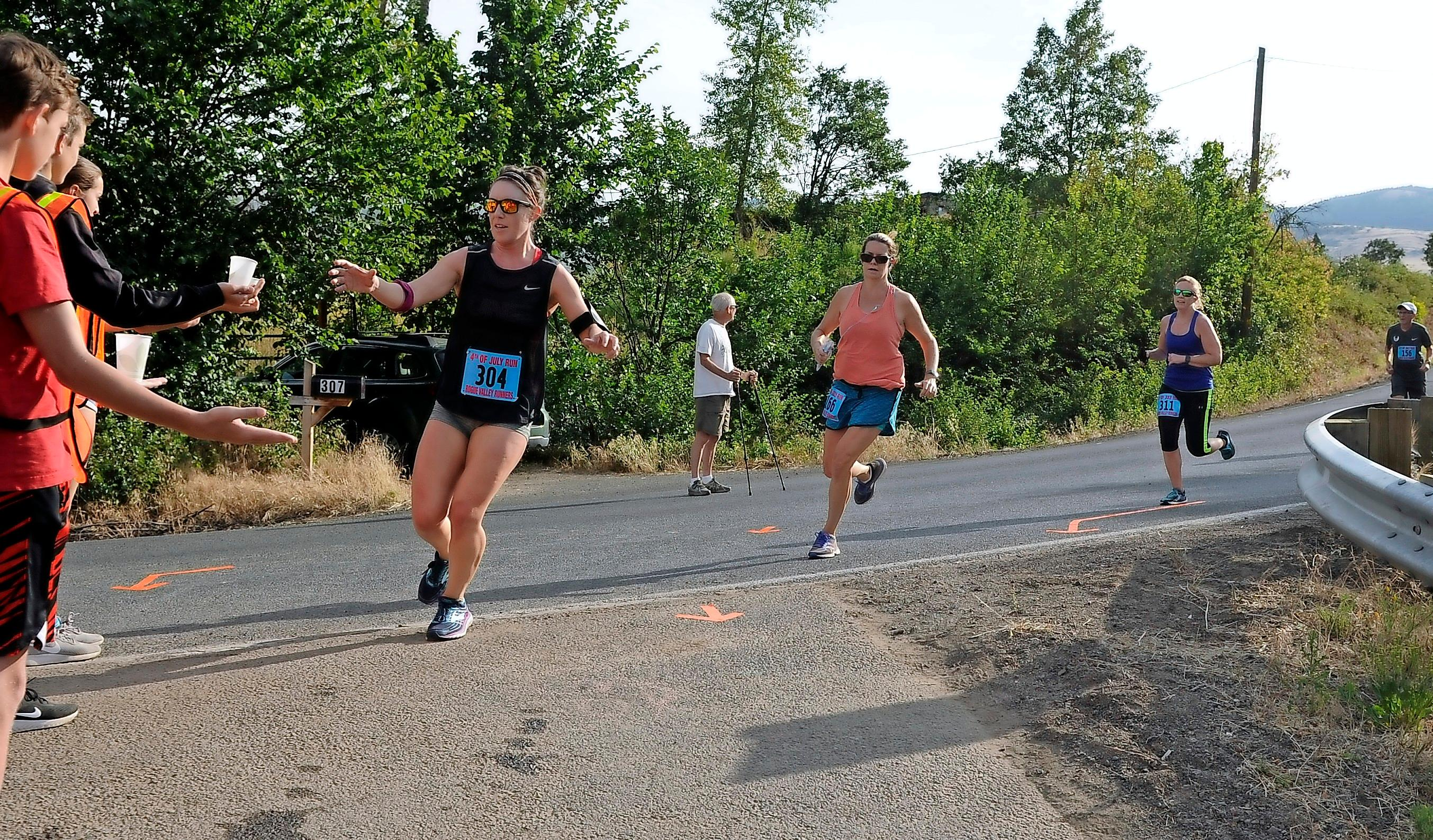 Andy Atkinson/Daily Tidings<br>Runners get some water at the turn-around at the Ashland 4th of July Run 10k Wednesday morning.