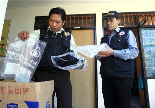 Indonesian forensic police officers view evidence related to the death of an American woman in Bali, Indonesia.