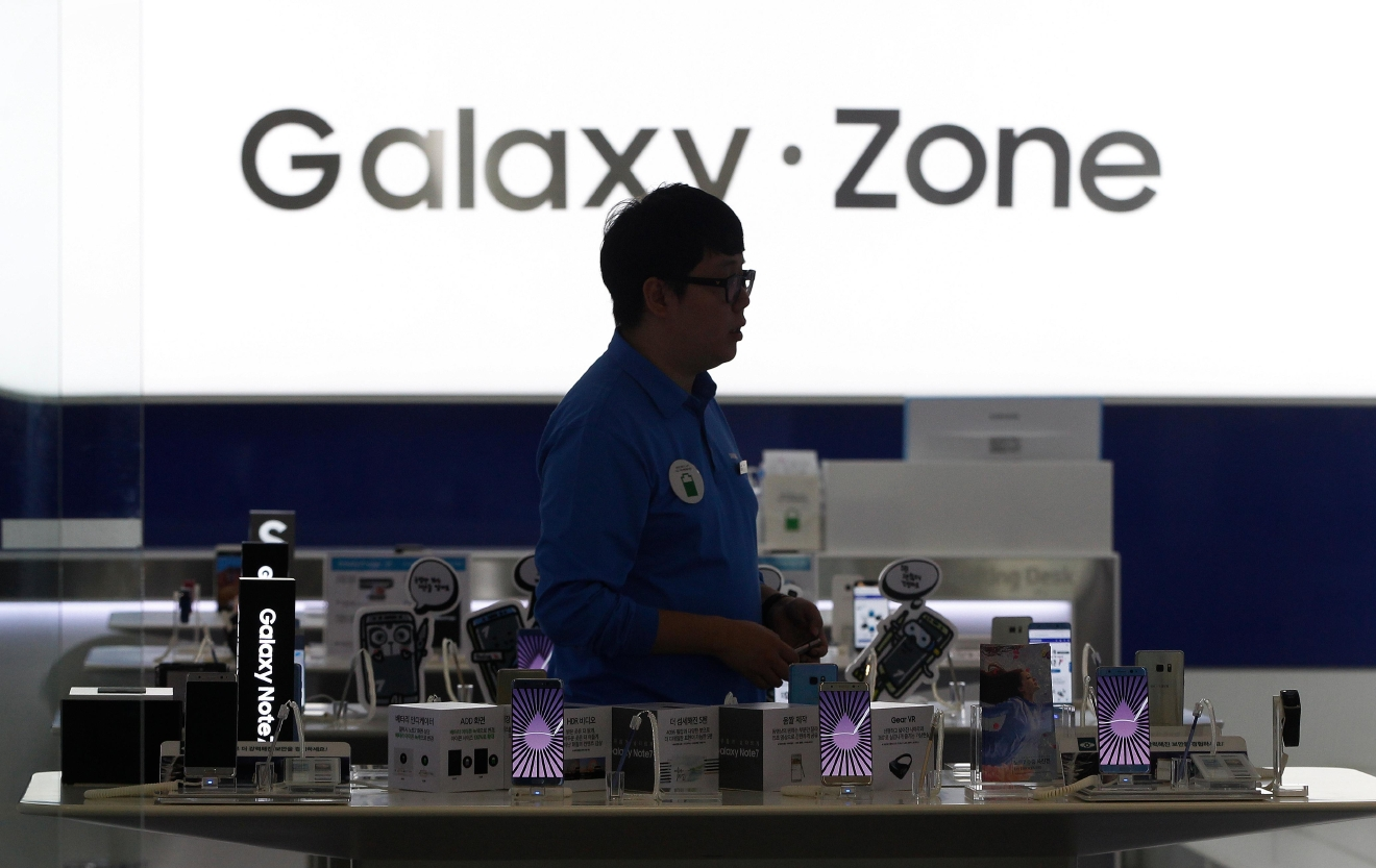 A man passes by Samsung Electronics Galaxy Note 7 smartphones at the company's shop in Seoul, South Korea, Monday, Oct. 10, 2016. Samsung Electronics has temporarily halted production of its Galaxy Note 7 smartphones, South Korea's Yonhap news agency reported Monday, following reports that replacements for the fire-prone phones were also overheating. (AP Photo/Ahn Young-joon)