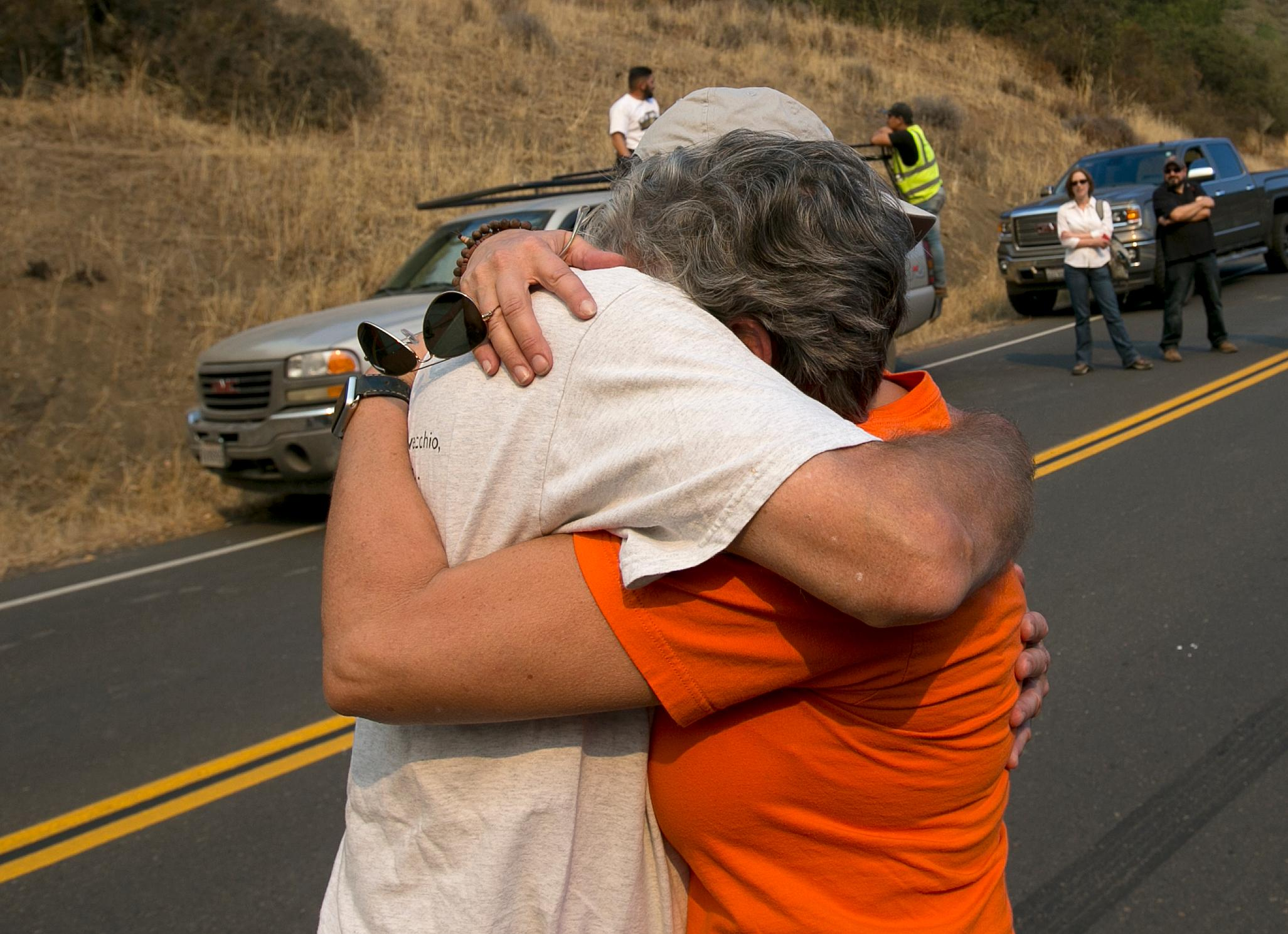 Laura Castellanos comforted by neighbor Mike Fisher, Friday, Oct., 13, 2017, after learning that her home was destroyed by the massive wildfire that swept through the hills near Oakville, Calif. Firefighters continue to battle blaze burning in the heart of California's wine country. Fishers home was sparred by the fire. (AP Photo/Rich Pedroncelli)