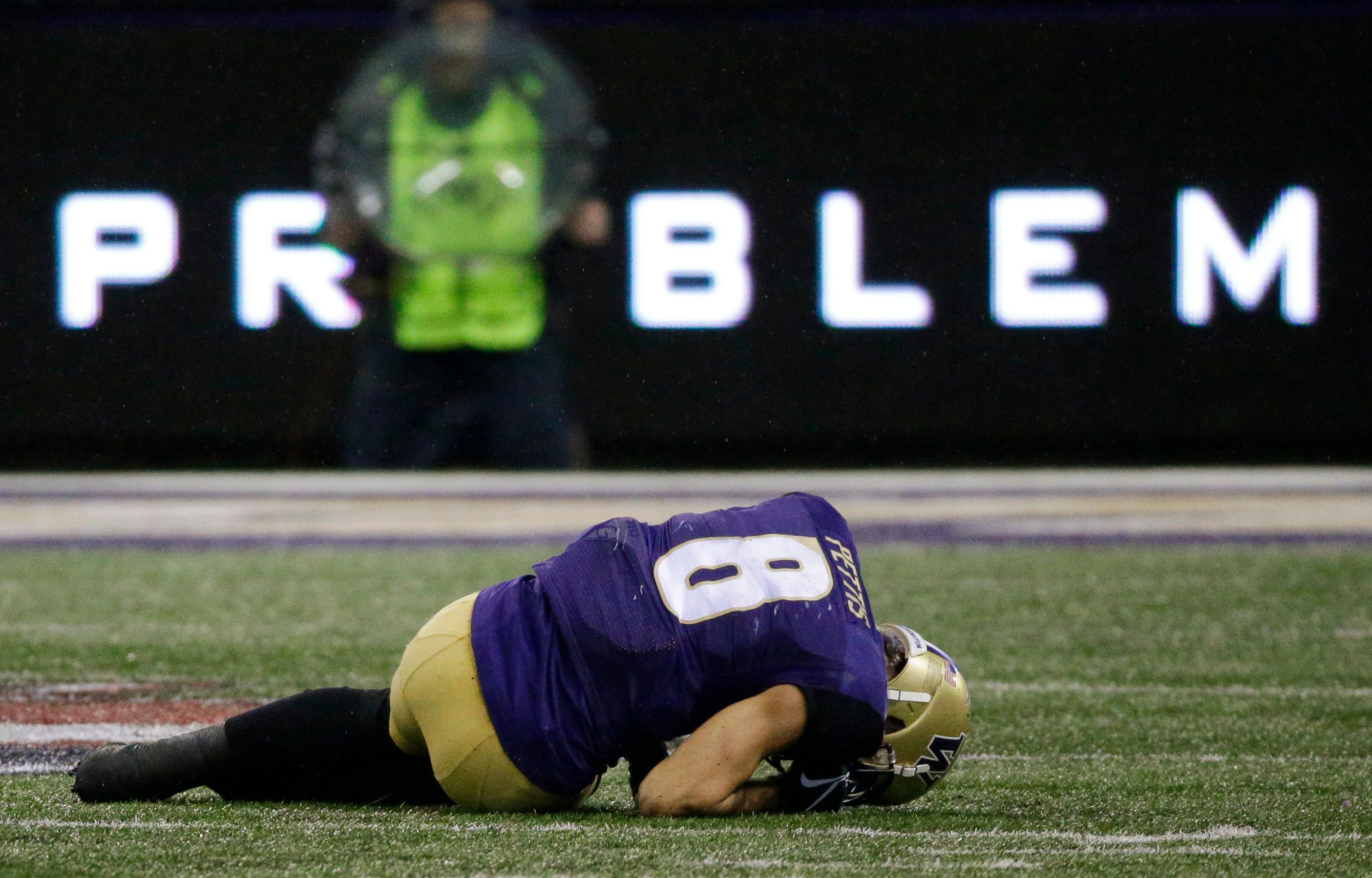 Washington wide receiver Dante Pettis curls up on the turf after an injury during the first half of an NCAA college football game against Washington State, Saturday, Nov. 25, 2017, in Seattle. Pettis left the field after the play. (AP Photo/Ted S. Warren)