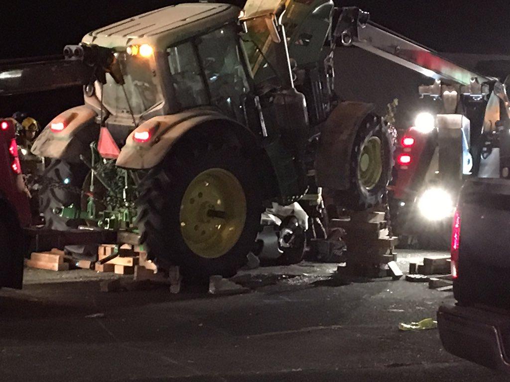 Crews in Gaston hoist a tractor up onto wooden blocks Wednesday night after it ran over a car, trapping two people. (Photo: Nate Bynum/KATU News)