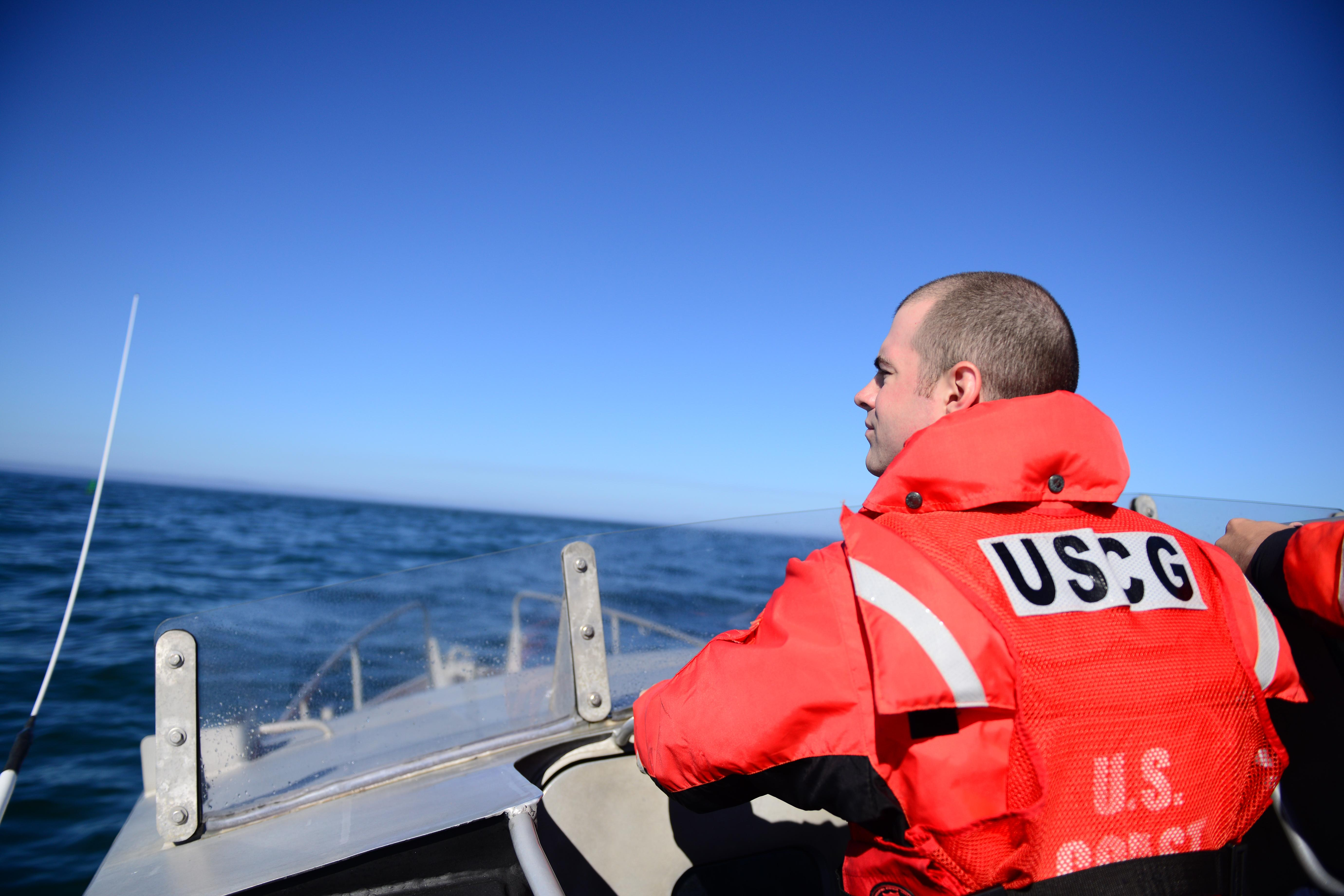 Seaman Cameron Smith, from Coast Guard Station Tillamook Bay, stands a lookout watch as a crewmember aboard a 47-foot Motor Lifeboat enroute to a training evolution in the Pacific Ocean near Garibaldi, Ore., Aug. 24, 2016.    The Tillamook Bay MLB crew trained with an MH-60 Jayhawk helicopter aircrew who practiced delivering a rescue basket to the boatcrew.    U.S. Coast Guard photo by Petty Officer 1st Class Levi Read.