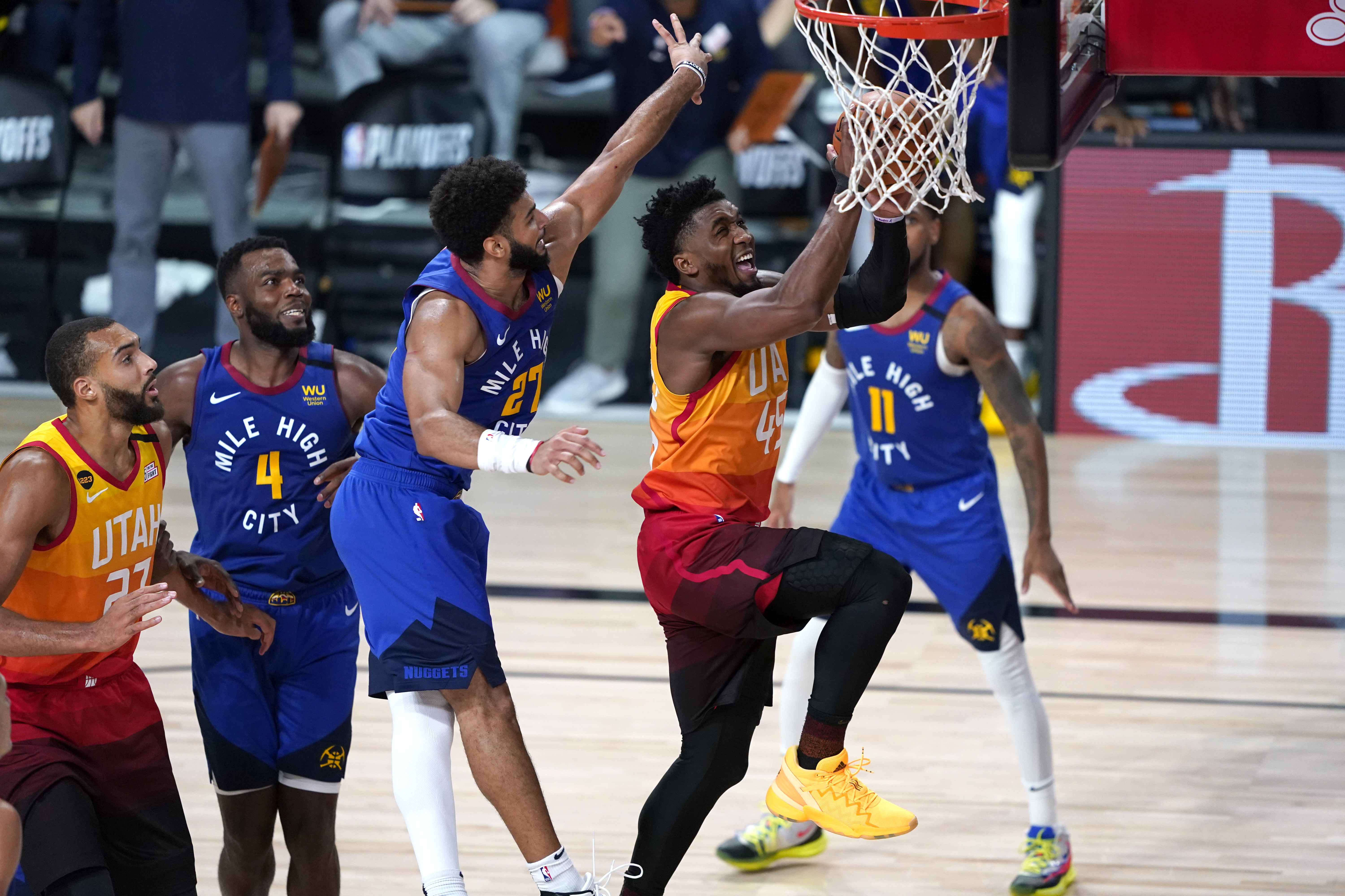 Utah Jazz's Donovan Mitchell (45) goes up for a shot as Denver Nuggets' Jamal Murray (27) defends during the second half of an NBA basketball first round playoff game Sunday, Aug. 23, 2020, in Lake Buena Vista, Fla. (AP Photo/Ashley Landis, Pool)