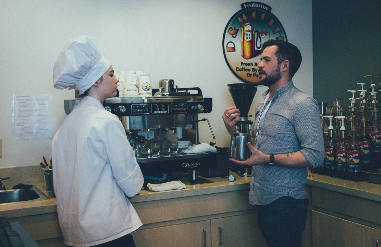 A YV Tech student and a member of the Washington STEM Learning Tour talk about different ways to prepare coffee at the YV Tech cafe. Pictured: A YV tech student and Danny Gross, Communications Manager at Washington STEM