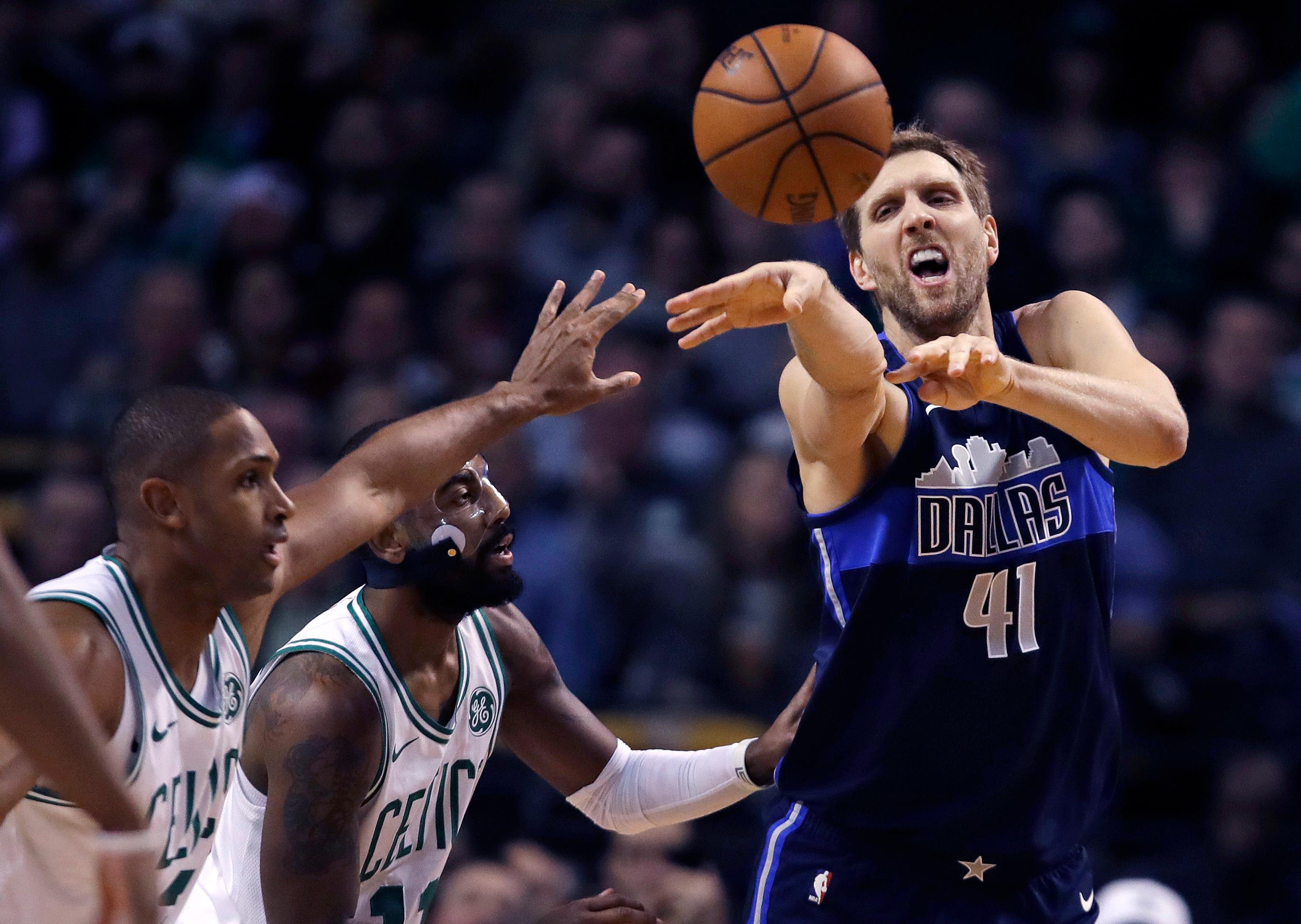 Dallas Mavericks forward Dirk Nowitzki (41) passes the ball while covered by Boston Celtics forward Al Horford, left, and guard Kyrie Irving during the first quarter of an NBA basketball game in Boston, Wednesday, Dec. 6, 2017. (AP Photo/Charles Krupa)