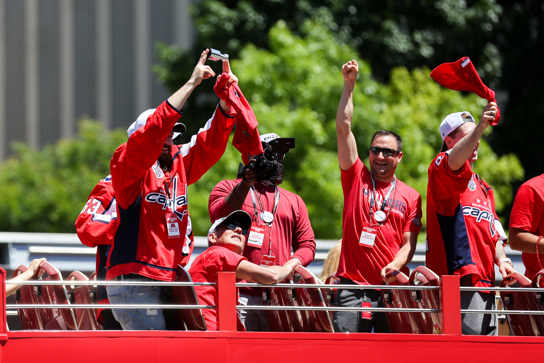 The National Mall was a sea of red as the Washington Capitals paraded the Stanley Cup through the streets of D.C. Although the cup barely left Alex Ovechkin's brawny-but-tender embrace, the players reveled in the fervor, shotgunning beers as they rode on top of buses along Constitution Avenue before rallying on The Mall. (Amanda Andrade-Rhoades/DC Refined)