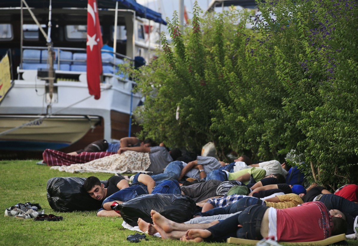 Migrants sleep on the marina promenade of the coastal town of Bodrum, Turkey, Sunday, Aug. 16, 2015. The city of Bodrum, a magnet for wealthy tourists, is these days drawing plenty of other visitorsó migrants fleeing conflicts in the Middle East and Africa and seeking a better life in Europe. At its closest point, the Greek island of Kos is only 4 kilometers (2.5 miles) from Turkey and migrants, mostly from Syria, but also from Afghanistan, Iran and African nations often try to cross in groups upward of eight people in small inflatable plastic boats meant for a maximum of four, powered by tiny electric outboard motors and plastic paddles.(AP Photo/Lefteris Pitarakis)