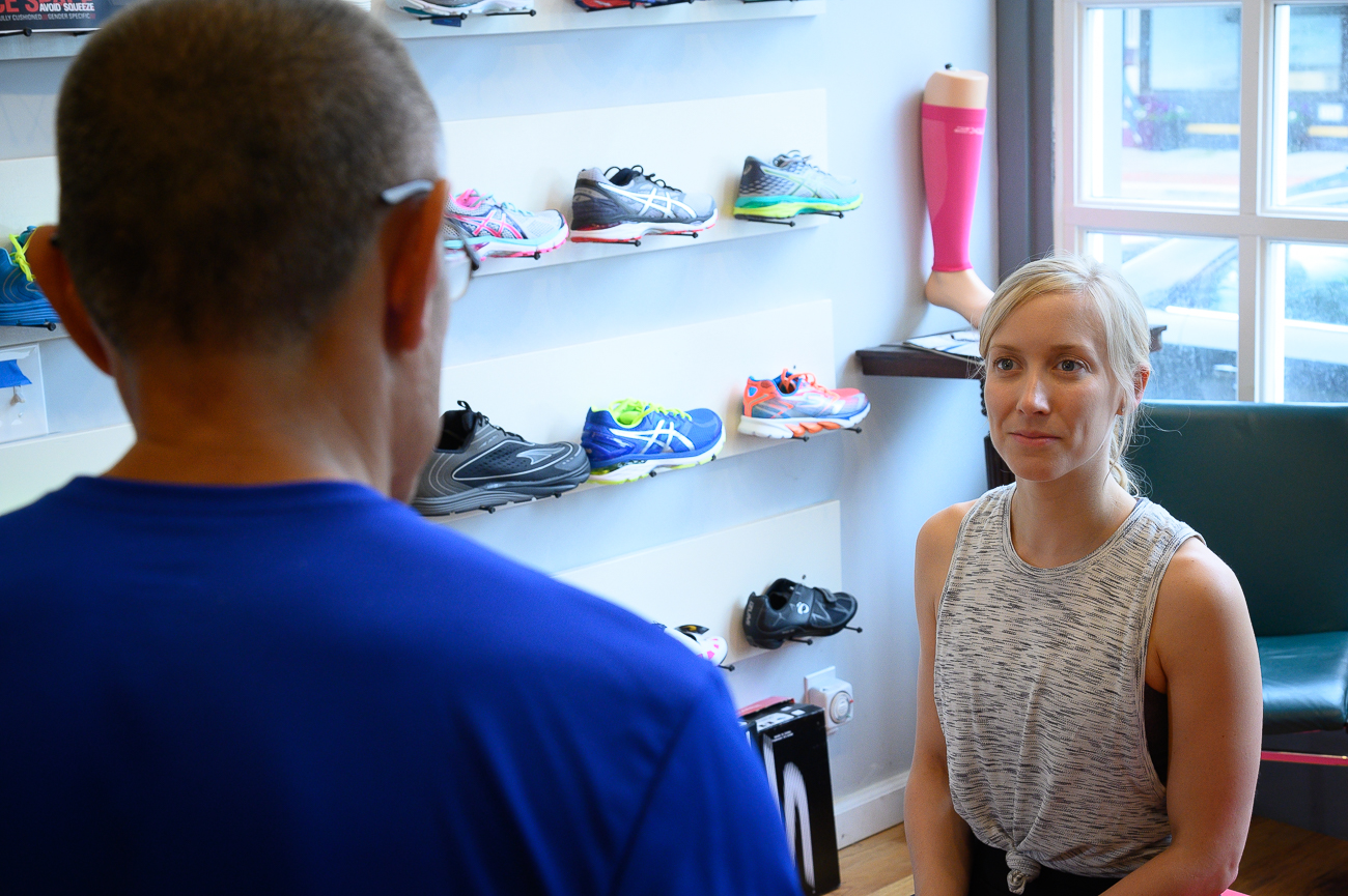 Owner Joe Fung explains to Lauren Pax the type of shoe she needs to properly support her as she runs. / Image: Phil Armstrong, Cincinnati Refined // Published: 5.30.19
