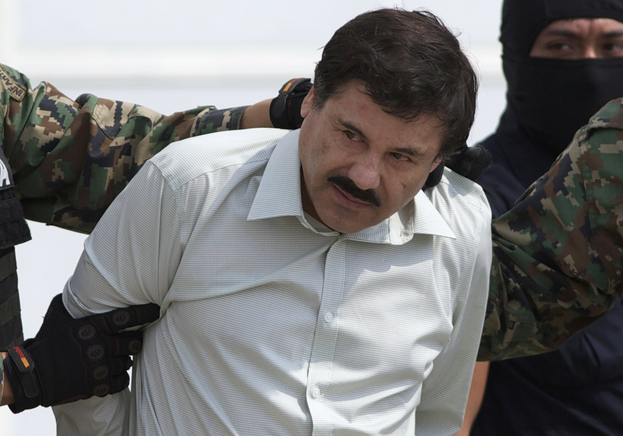 "FILE - This Feb. 22, 2014 file photo shows Joaquin ""El Chapo"" Guzman, the head of Mexico's Sinaloa Cartel, being escorted to a helicopter in Mexico City following his capture overnight in the beach resort town of Mazatlan. Ten years after it began, Mexico's drug war has left some major drug cartels splintered and many of the old-line capos in jail, but it has done little to reduce the amount of crime or violence in Mexico's roughest regions. (AP Photo/Eduardo Verdugo, File)"