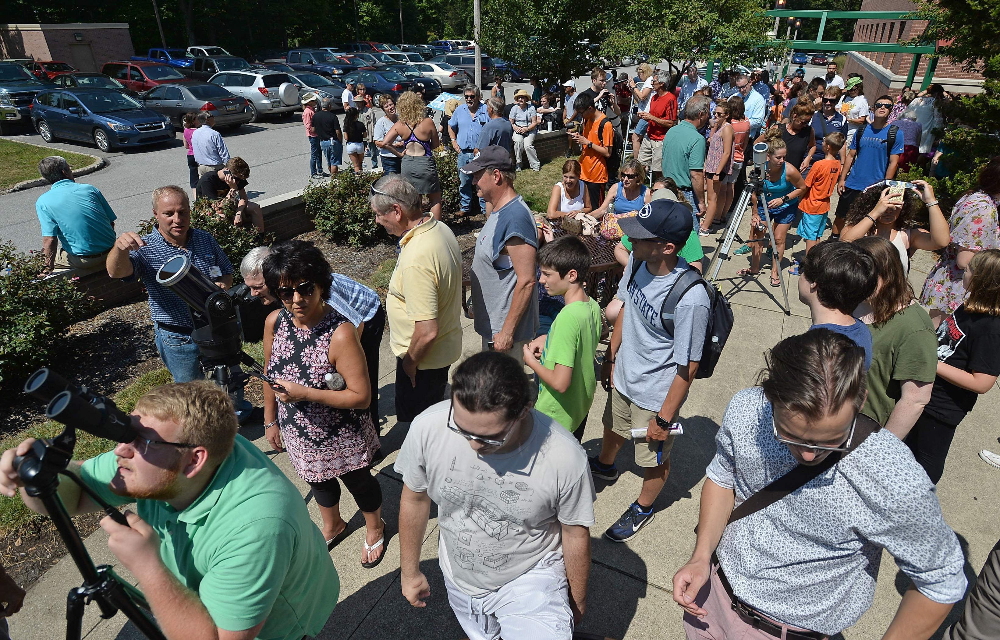 Hundreds turned out Aug. 21 at an eclipse-viewing party held at Penn State Behrend in Harborcreek Township, which featured telescopes fitted with solar filters available for viewing the partial eclipse. [CHRISTOPHER MILLETTE/ERIE TIMES-NEWS]