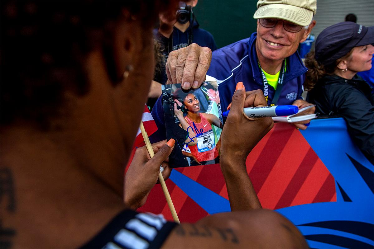 Nike's Brianna Rollins autographs a picture of herself for a fan on her victory lap. Rollins won the 100 meter hurdles with a time of 12.34. Photo by August Frank, Oregon News Lab