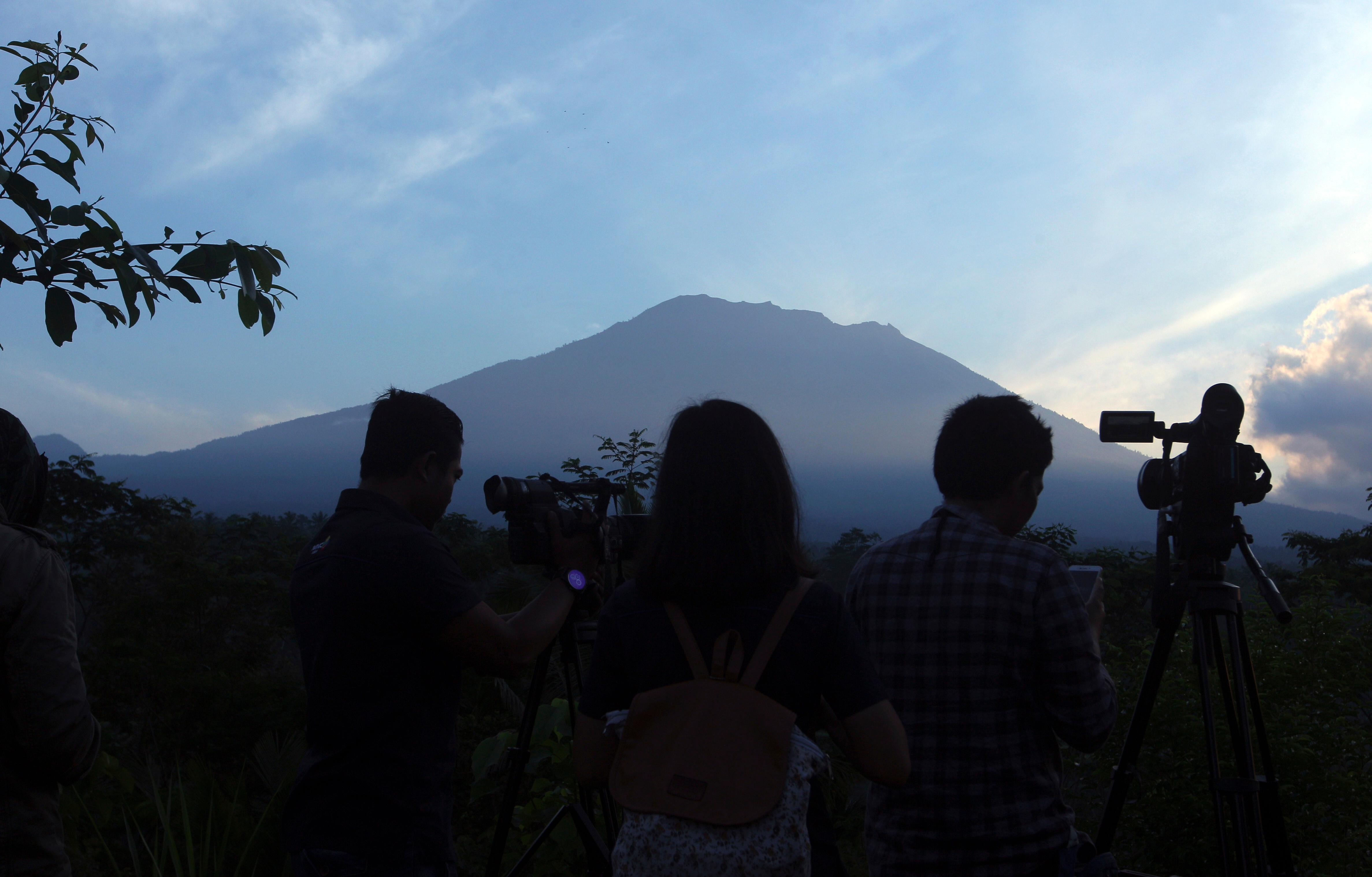 Journalists watch Mount Agung from an observation point which is about 12 kilometer (7.4 miles) away from the volcano in Karangasem, Bali, Indonesia, Thursday, Sept. 28, 2017. The exodus from the menacing volcano on the Indonesian tourist island is nearing 100,000 people, a disaster official said Wednesday, as hundreds of tremors from the mountain are recorded daily. (AP Photo/Firdia Lisnawati)