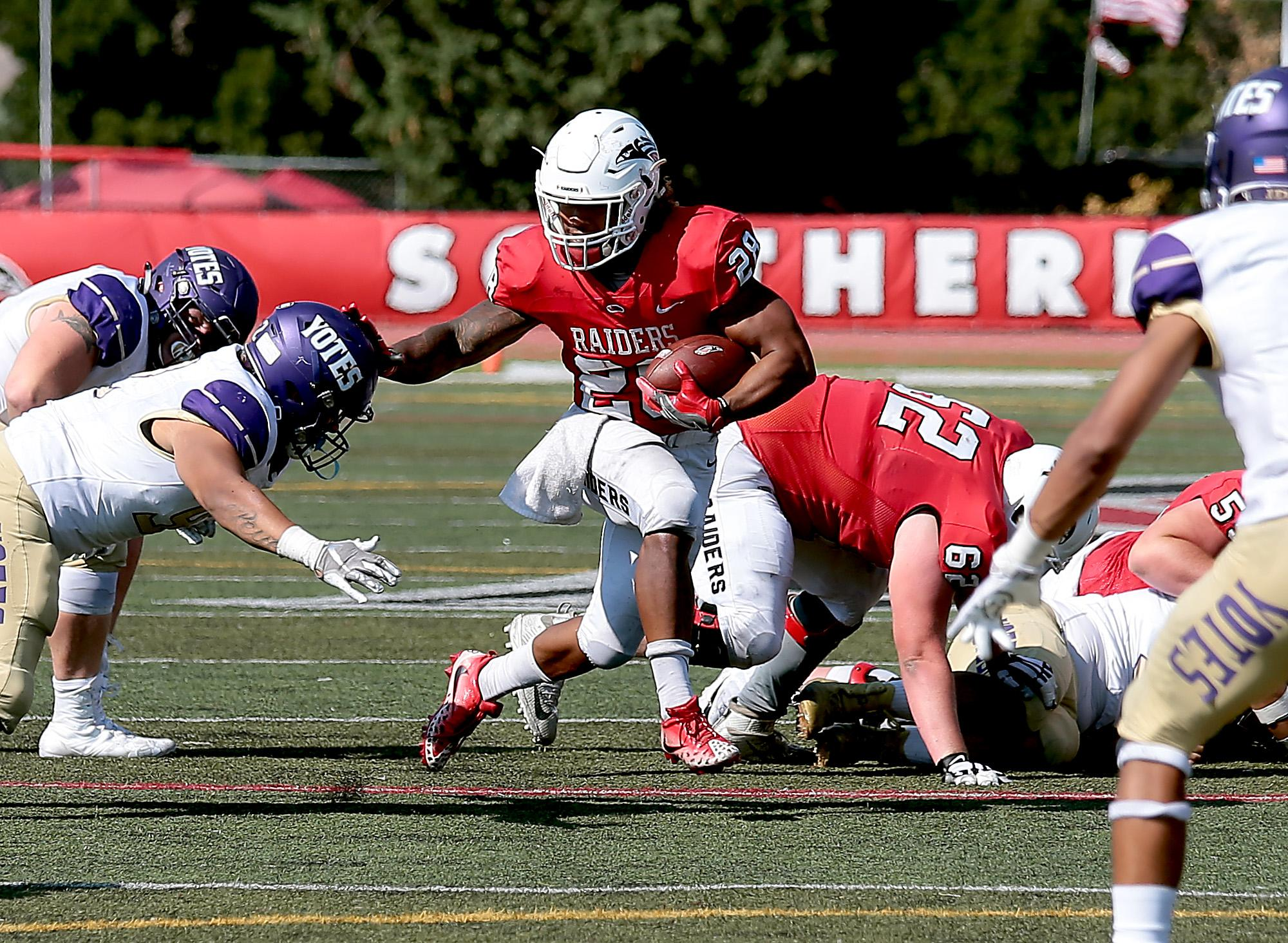 Larry Stauth Jr./For the Daily TidingsSouthern Oregon University senior running back Rey Vega fights his way through The College of Idaho defense en route to his second touchdown of the day at Raider Stadium on Saturday.