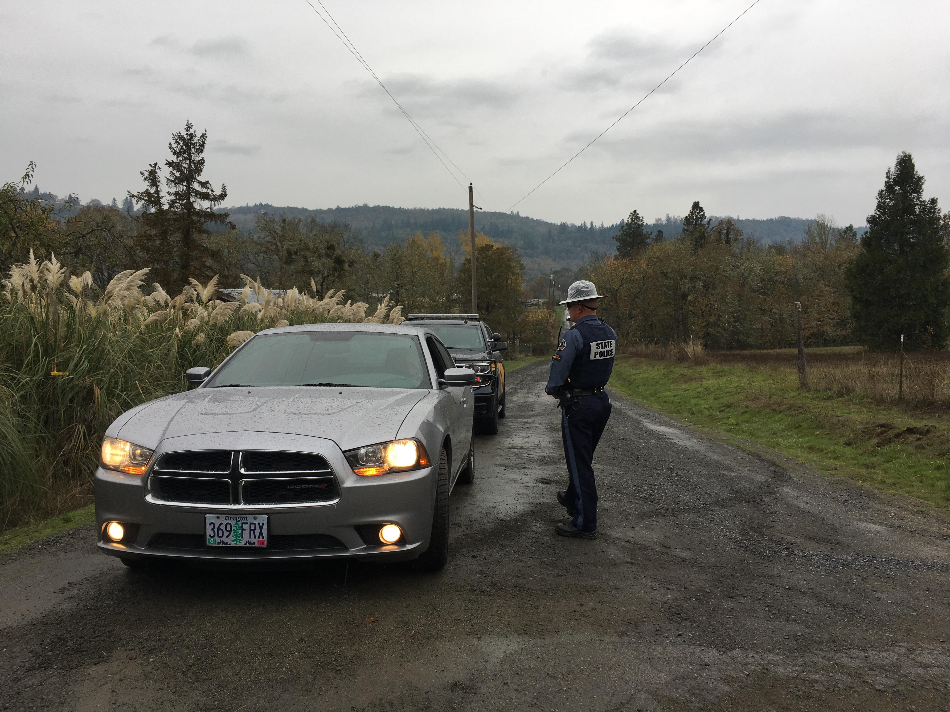 Troopers close off the road in Lookingglass as they continue investigating a triple homicide, Nov. 8, 2017. (SBG)