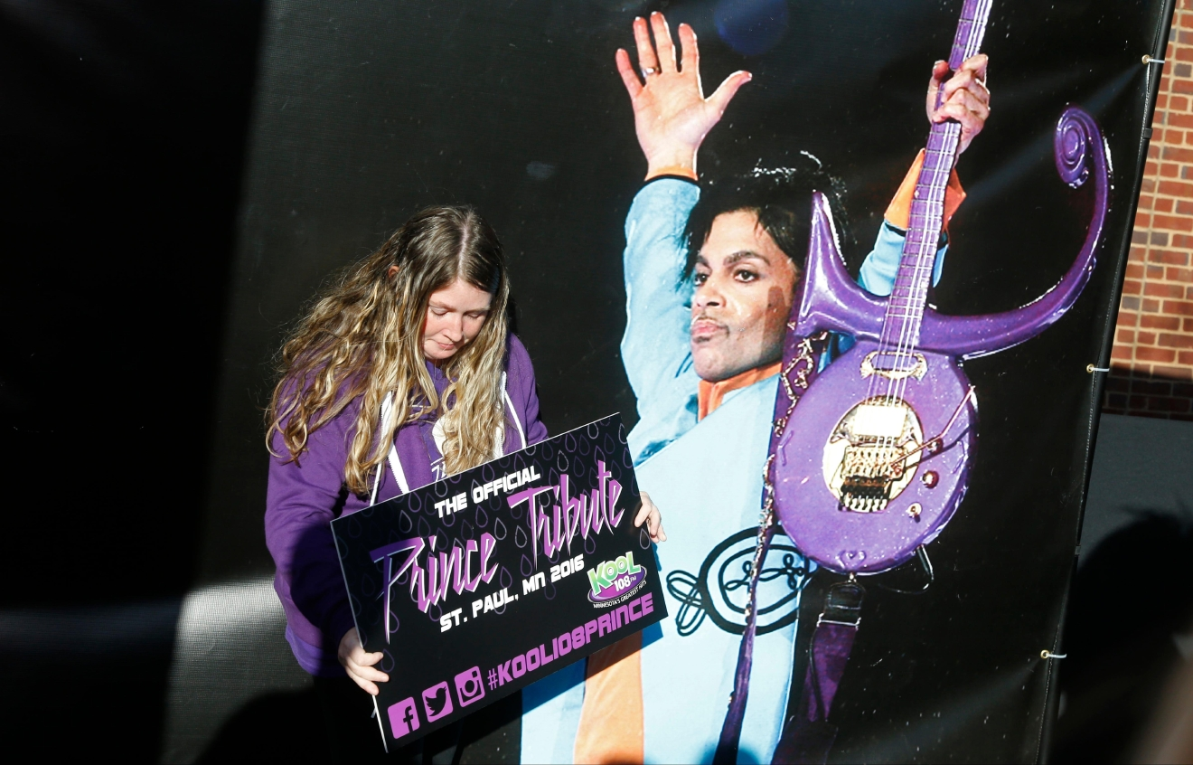 A Prince fan poses with a large photo backdrop of the late Prince as fans gather outside Xcel Arena Thursday, Oct. 13, 2016, in St. Paul, Minn., waiting for a concert honoring the musician who died in April of accidental painkiller overdose. (AP Photo/Jim Mone)