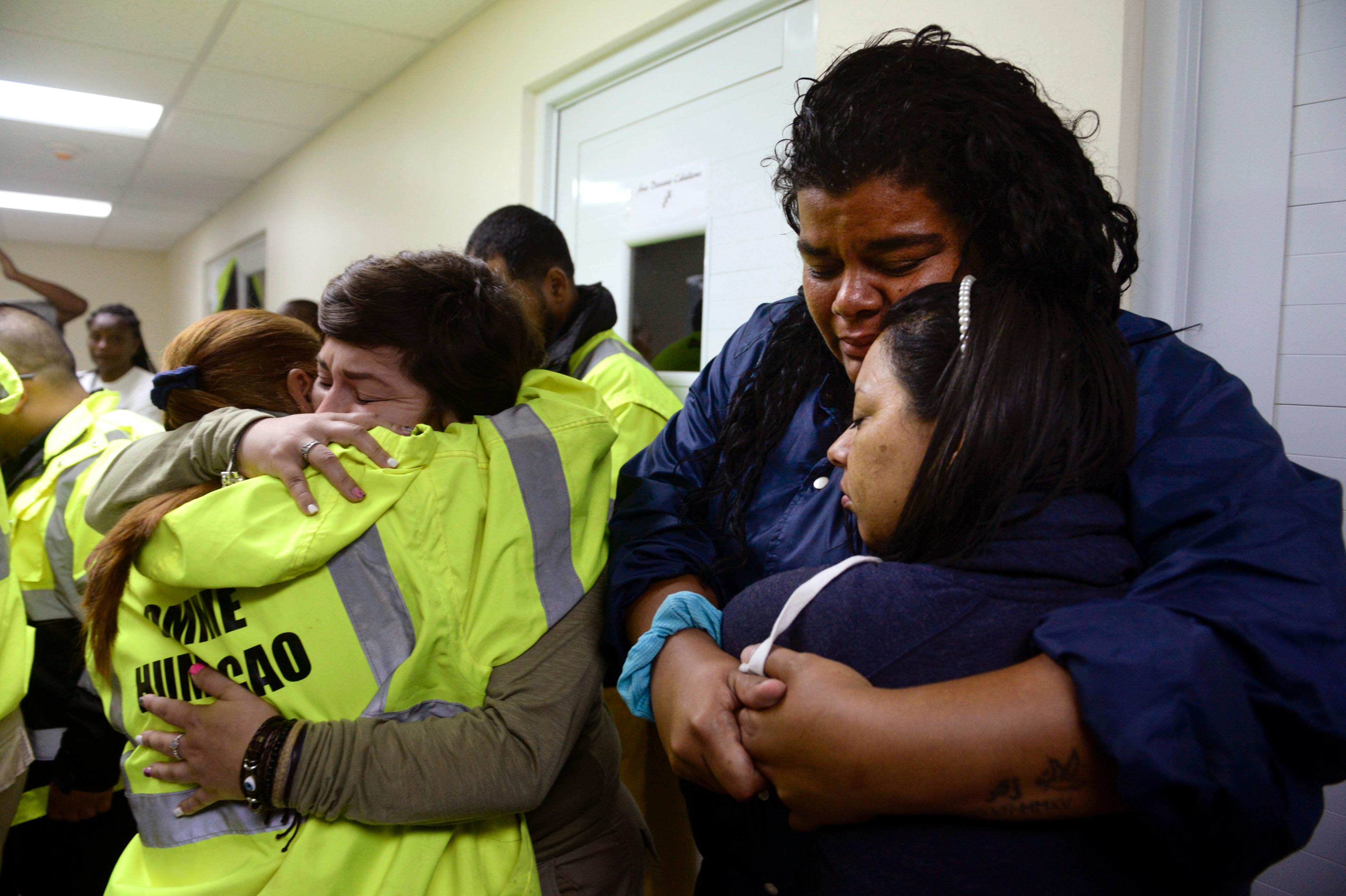 In this Sept. 20, 2017 photo, rescue team members Candida Lozada, left, and Stephanie Rivera, second from left, Mary Rodriguez, second from right, and Zuly Ruiz, right, embrace as they wait to assist in the aftermath of Hurricane Maria in Humacao, Puerto Rico. (AP Photo/Carlos Giusti)