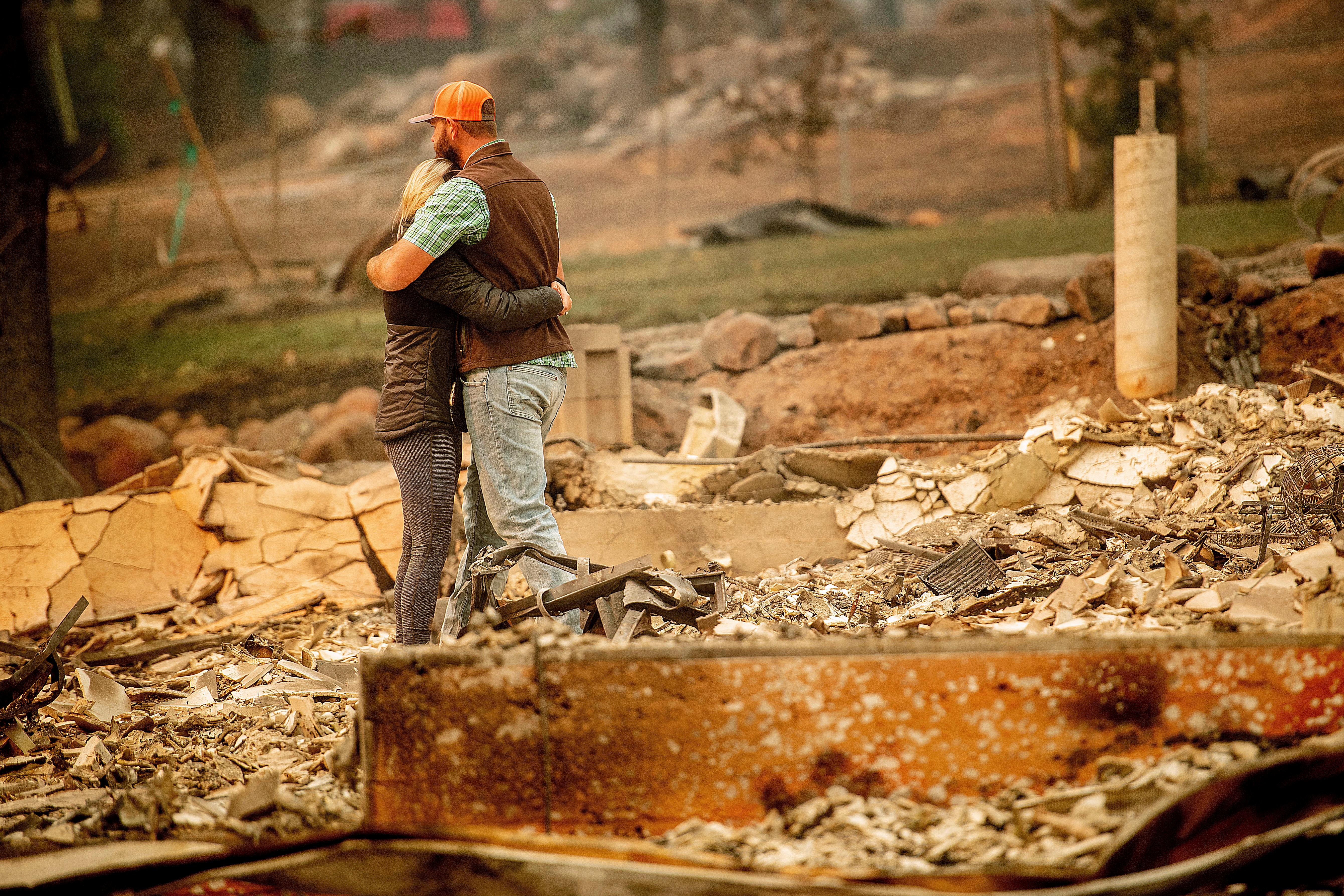 Chris and Nancy Brown embrace while searching through the remains of their home, leveled by the Camp Fire, in Paradise, Calif., on Monday, Nov. 12, 2018. As the fire approached, Nancy Brown escaped from the home with her 2-year-old and three dogs. (AP Photo/Noah Berger)