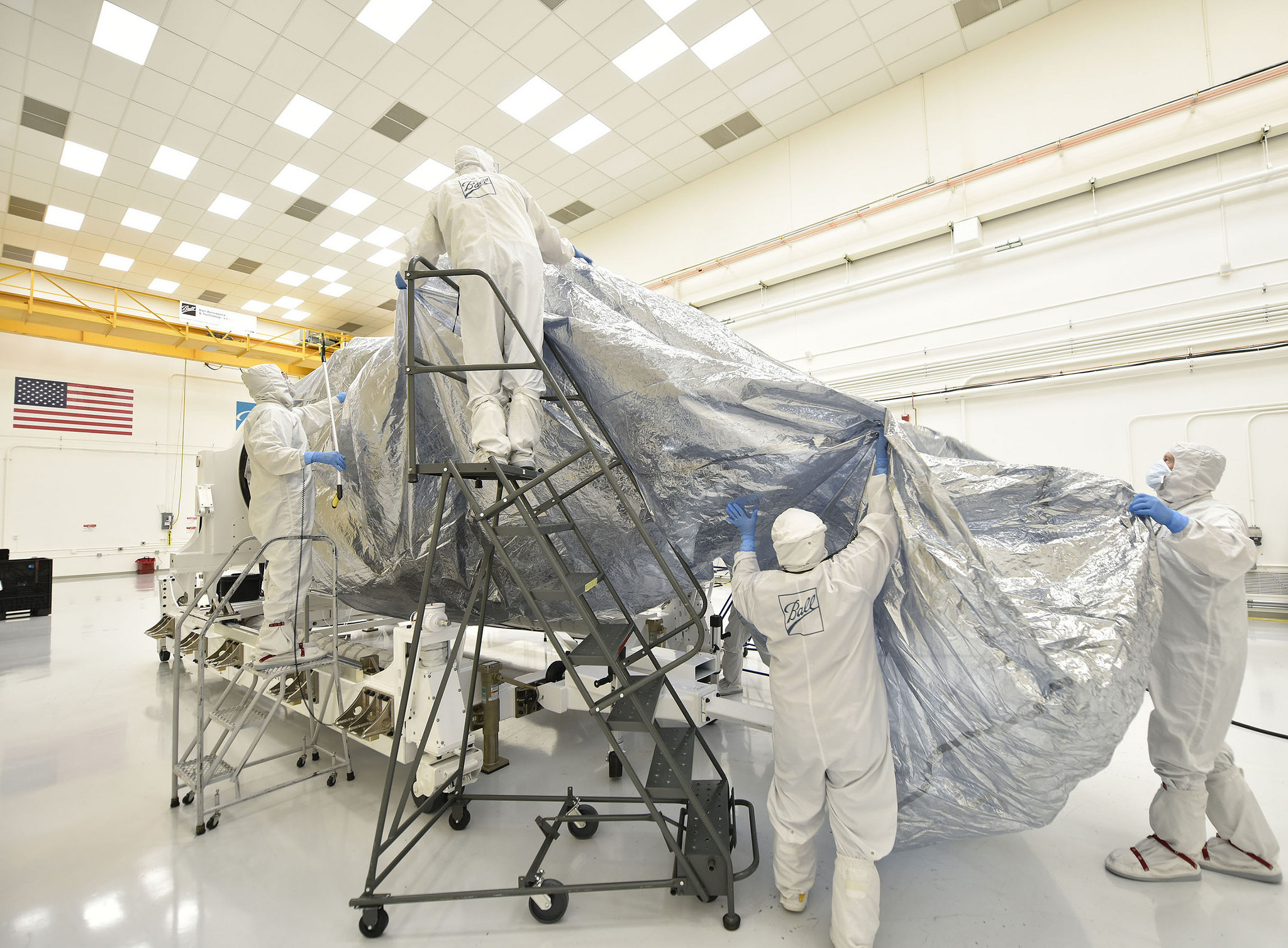 "The Ball Aerospace team begins bagging the JPSS-1 satellite with protective wrapping in preparation for shipment from Colorado to Vandenberg Air Force Base. The ""bag"" in which the satellite is wrapped is designed to protect it from electrostatic charges. Arcing from electrostatic discharge (ESD) can damage sensitive electronics.The cover material protects the satellite from ESD. (NASA Photo)"