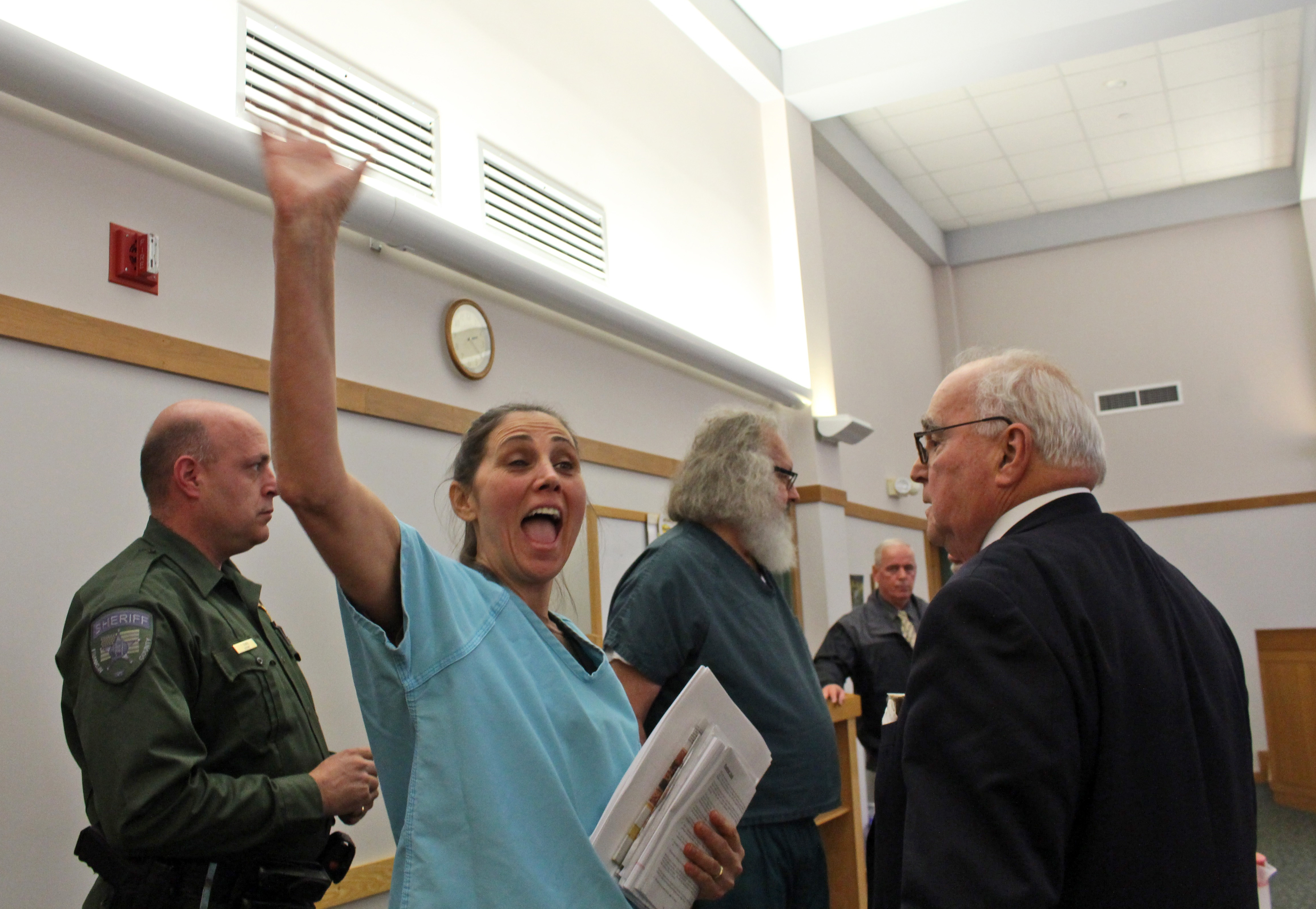 Evi Quaid, center left, waves after she and her husband actor Randy Quaid, center rear, had their handcuffs removed in court ,Thursday, Oct. 15, 2015, in St. Albans, Vt. A Vermont judge released the couple, who says they'll now address 5-year-old criminal charges in California.  (Elodie Reed/St. Albans Messenger via AP, Pool)