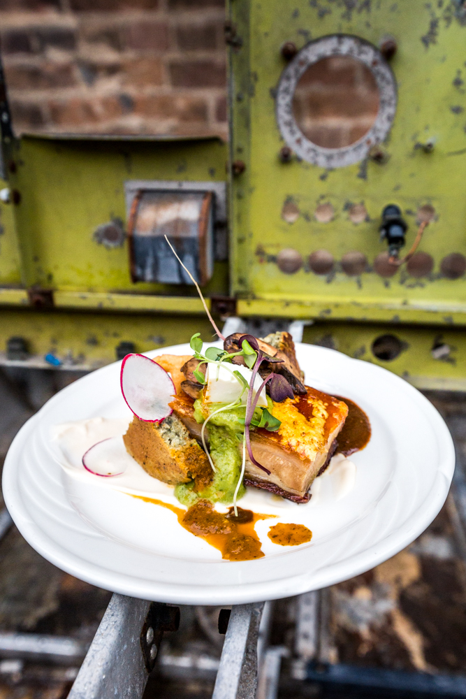 Mole Negro: pork belly, panela, micro flowers, crema, salsa, bean puree, corn cake, queso fresco, radishes, chicharron chip, and cilantro flowers / Image: Catherine Viox{ }// Published: 6.18.19