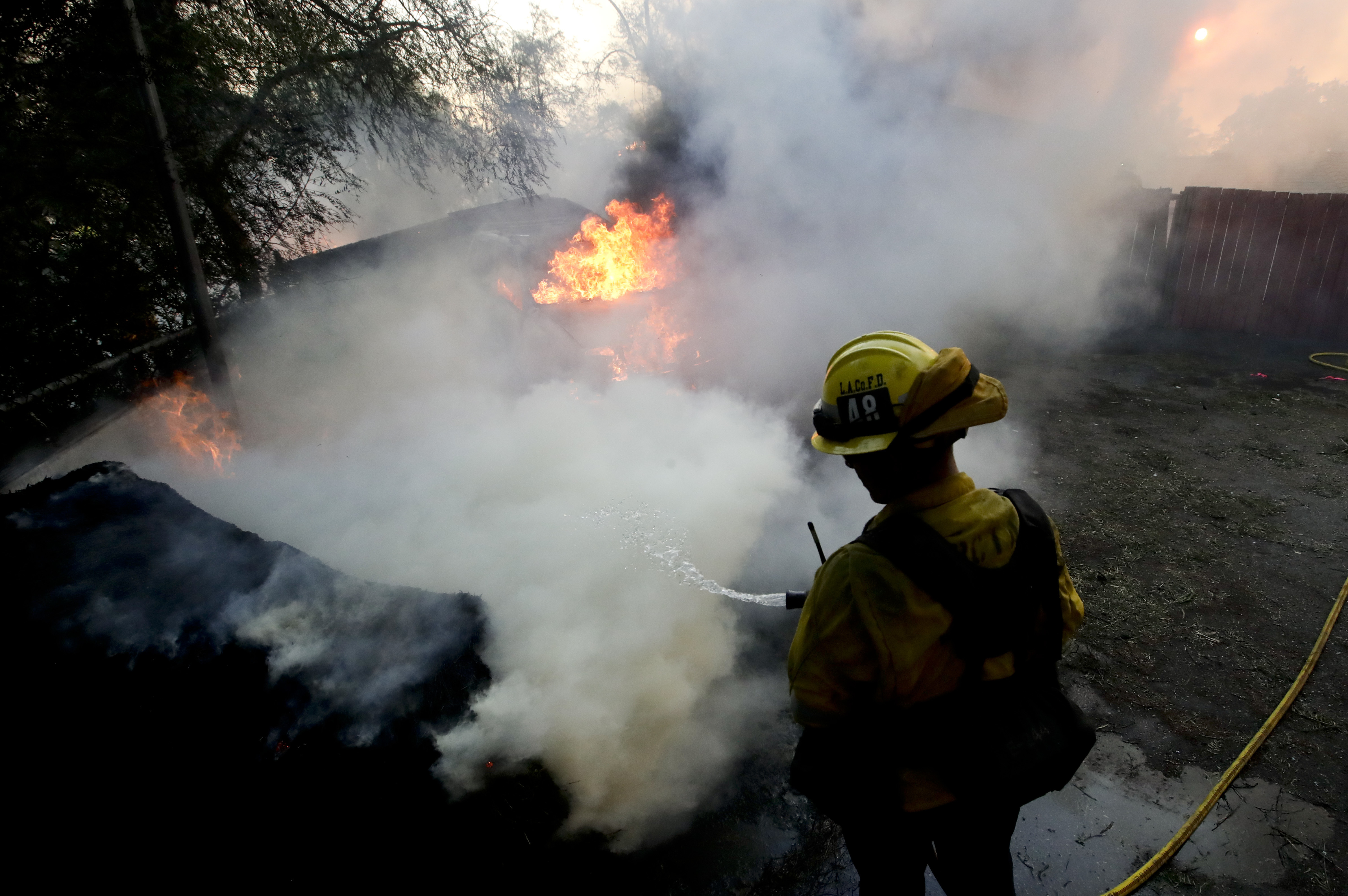 A Los Angeles County firefighter puts water on a burning car during a wildfire in the Lake View Terrace area of Los Angeles Tuesday, Dec. 5, 2017. For the second time in two months, wind-driven fires tore through California communities in the middle of the night, leaving rows of homes and a psychiatric hospital in ruins Tuesday and sending tens of thousands of people fleeing for their lives. (AP Photo/Chris Carlson)