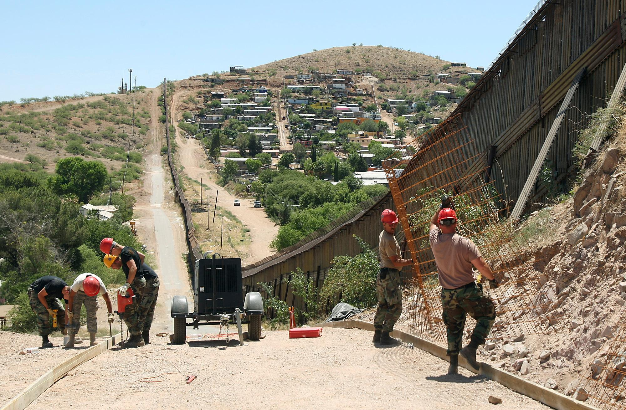 FILE - In this June 20, 2008 file photo, members of the 200th Red Horse Air National Guard Civil Engineering Squadron from Camp Perry in Ohio, including Tech Sgt. David Hughes, right, and Tech Sgt. William Bunker, second from right, work on building a road at the border in Nogales, Ariz. President Donald Trump said April 3, 2018, he wants to use the military to secure the U.S.-Mexico border until his promised border wall is built. The Department of Homeland Security and White House did not immediately respond to requests for comment. At the Pentagon, officials were struggling to answer questions about the plan, including rudimentary details on whether it would involve National Guard members, as similar programs in the past have done. But officials appeared to be considering a model similar to a 2006 operation in which former President George W. Bush deployed National Guard troops to the southern border in an effort to increase security and surveillance. (AP Photo/Ross D. Franklin, file)
