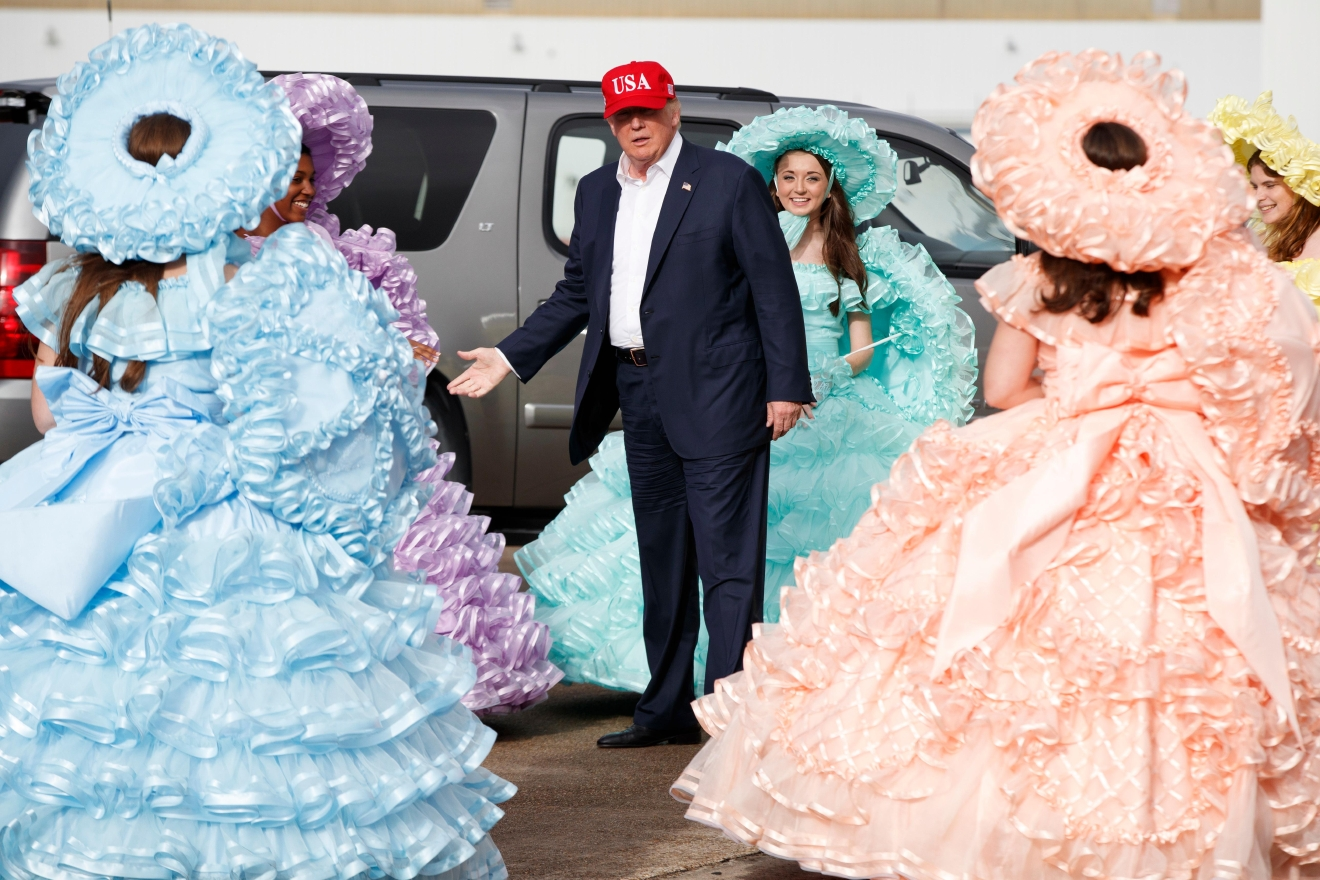 President-elect Donald Trump is greeted by the Azalea Trail Maids after arriving at the airport for a rally at Ladd-Peebles Stadium, Saturday, Dec. 17, 2016, in Mobile, Al. (AP Photo/Evan Vucci)