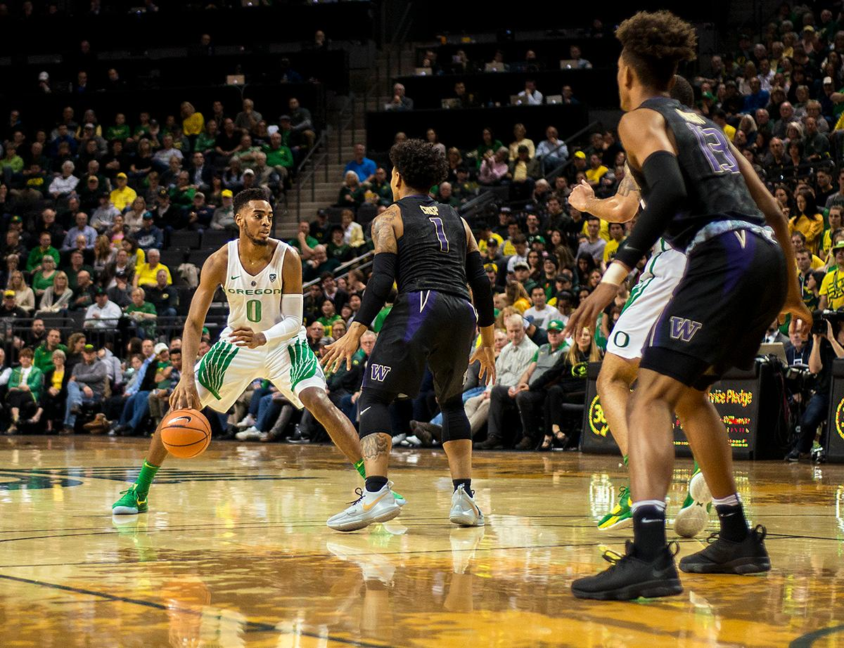 Oregon Ducks forward Troy Brown, Jr., (#0) looks for the best path to score as Washington Huskies guard David Crisp (#1) defends. The Oregon Ducks defeated the Washington Huskies 65-40 on Thursday night at Matthew Knight Arena. Troy Brown, Junior led Oregon with 21 points to match his career high, and Kenny Wooten set a career best of seven shots blocked. The Ducks now stand 6-5 in the Pac-12 conference play. Photo by Abigail Winn, Oregon News Lab
