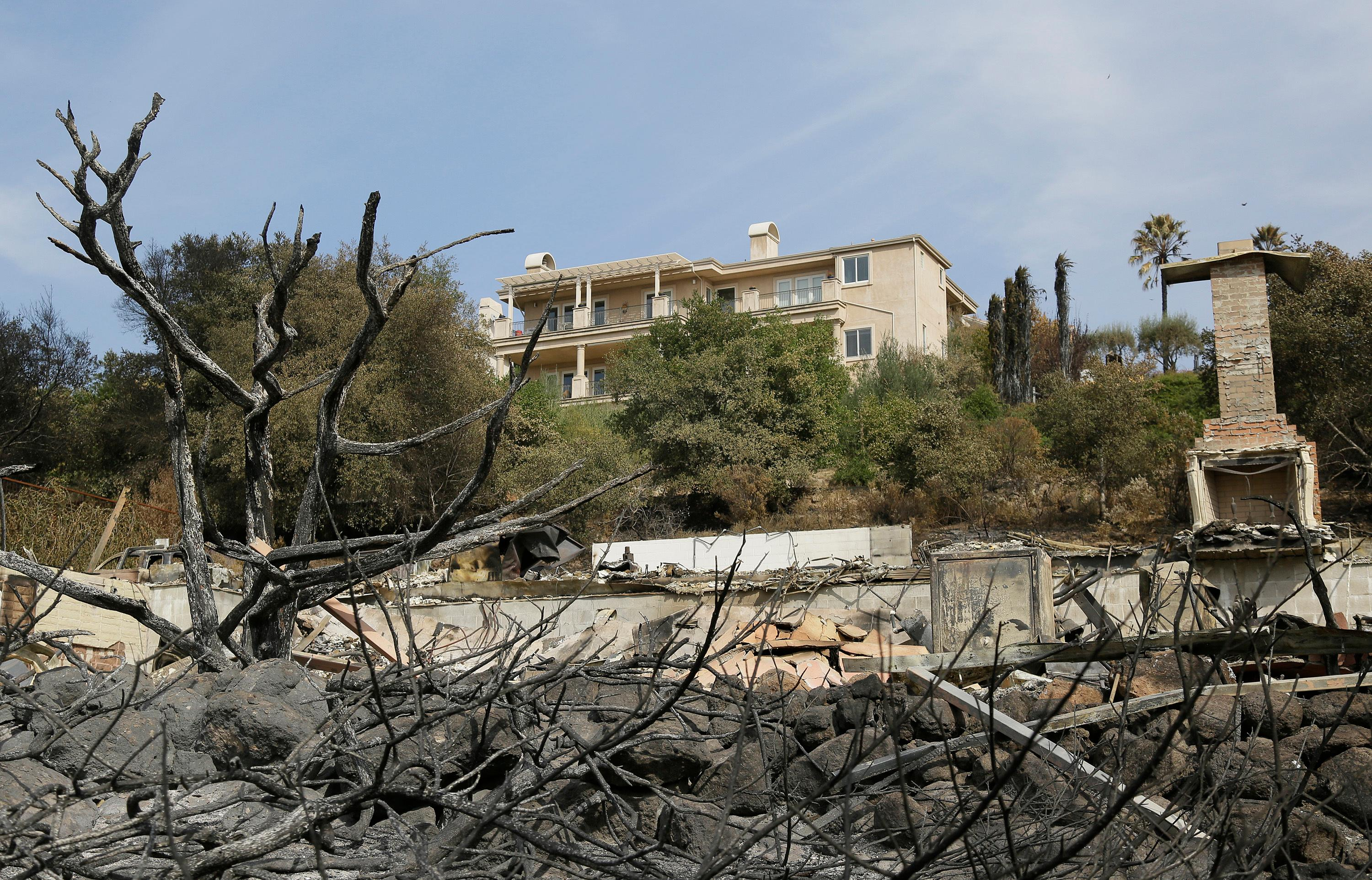 A house stands intact above one that was destroyed by wildfire near Atlas Peak Road, Monday, Oct. 16, 2017, in Napa, Calif. State and local officials say they are trying to get people back into their homes, but they cautioned that it could take days and even weeks for neighborhoods hard hit by Northern California wildfires. (AP Photo/Eric Risberg)