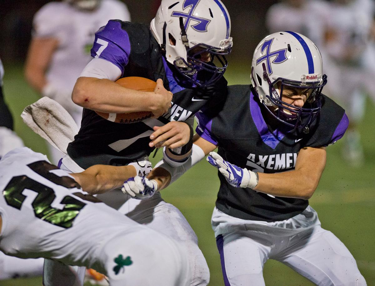 South Eugene Axemen quarterback Bryce Boettcher (#7) attempts to escape the grasp of Sheldon Irish defensive back Ben Mehlhaff (#25). Sheldon defeated South Eugene 63-6. Photo by Dan Morrison, Oregon News Lab
