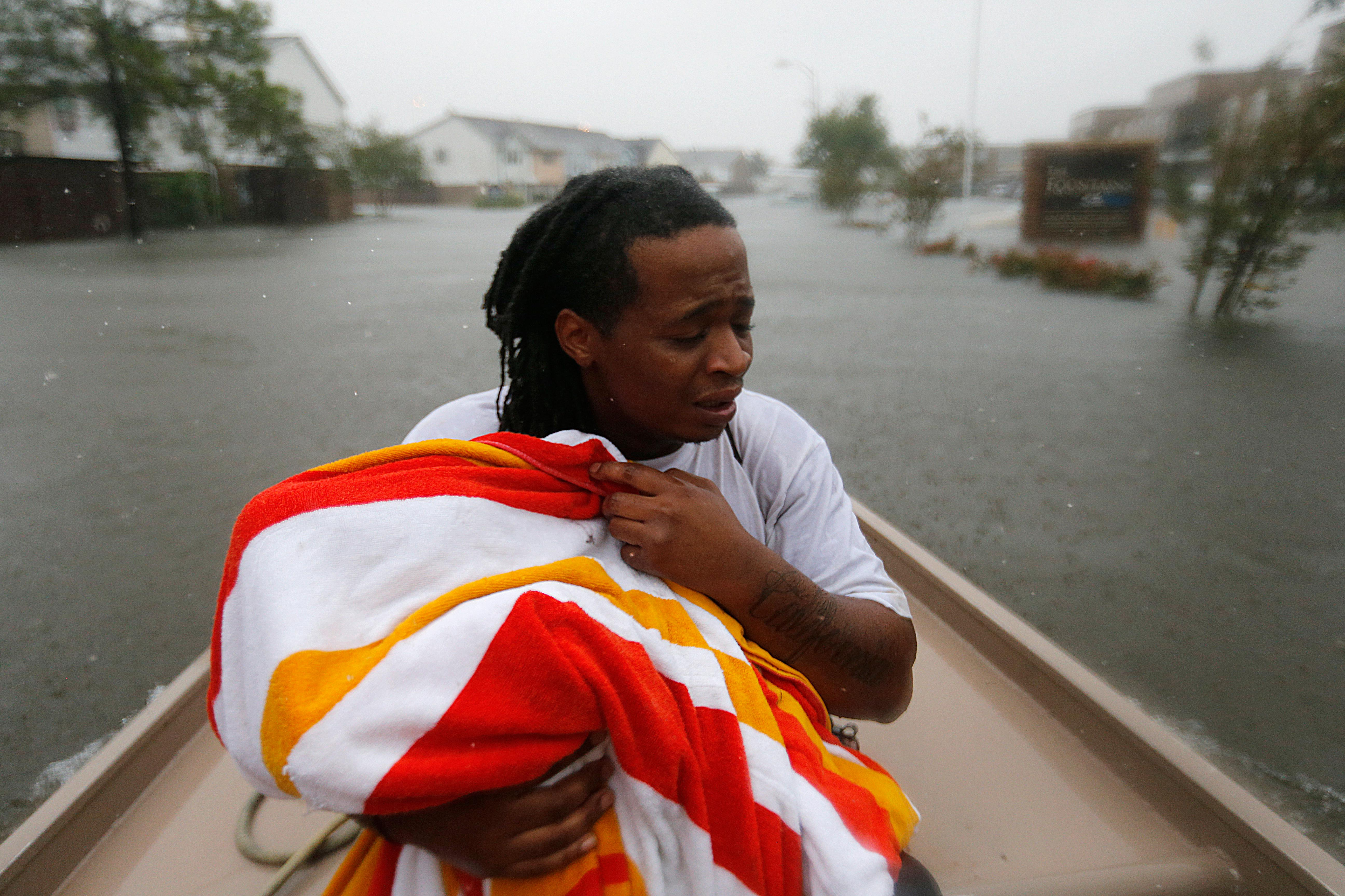 Demetres Fair holds a towel over his daughter Damouri Fair, 2, as they are rescued by boat by members of the Louisiana Department of Wildlife and Fisheries and the Houston Fire Department during flooding from Tropical Storm Harvey in Houston, Monday, Aug. 28, 2017. (AP Photo/Gerald Herbert)