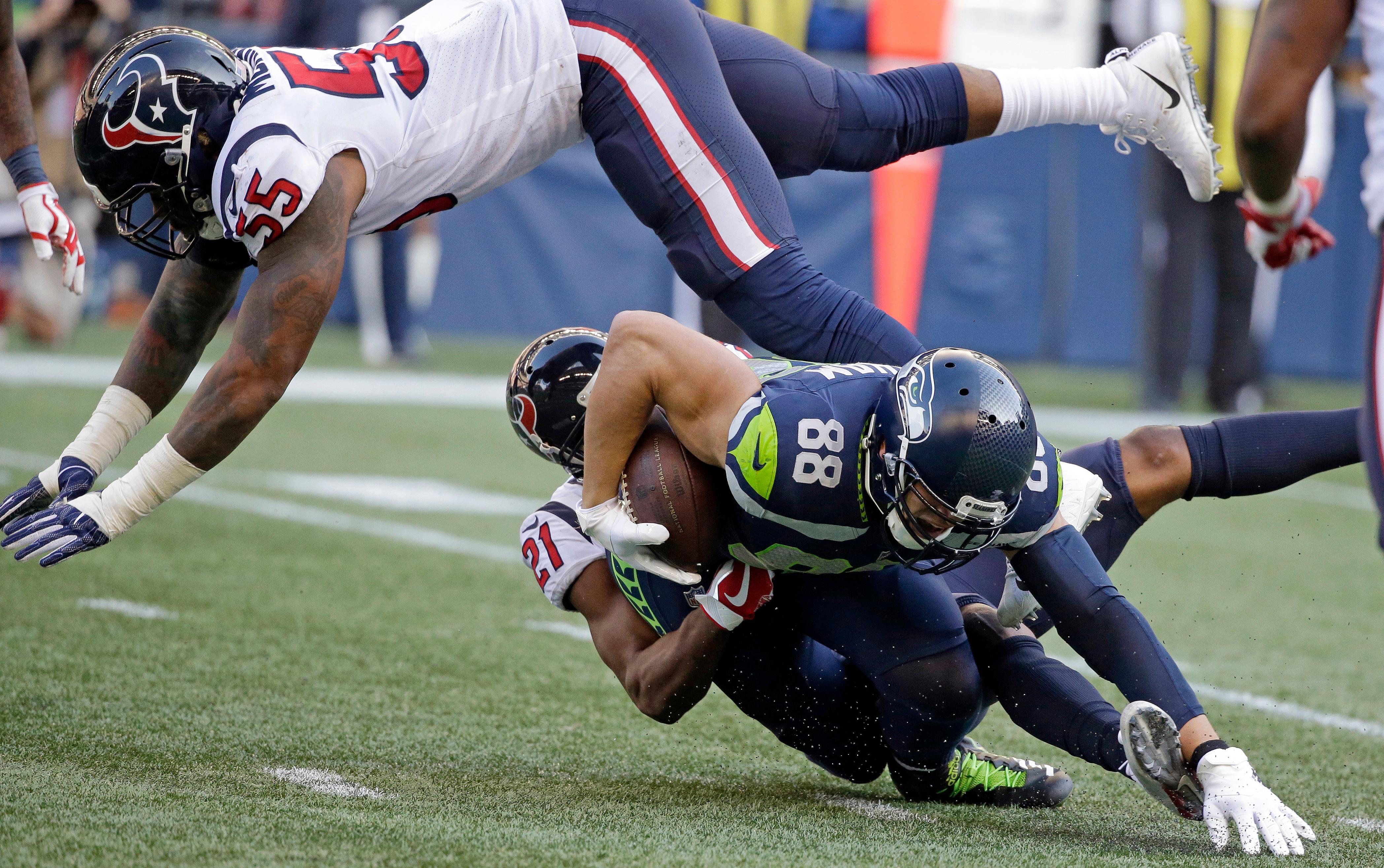 Seattle Seahawks tight end Jimmy Graham (88) is tackled by Houston Texans strong safety Marcus Gilchrist (21) as Texans inside linebacker Benardrick McKinney (55) leaps over them in the second half of an NFL football game, Sunday, Oct. 29, 2017, in Seattle. (AP Photo/Elaine Thompson)