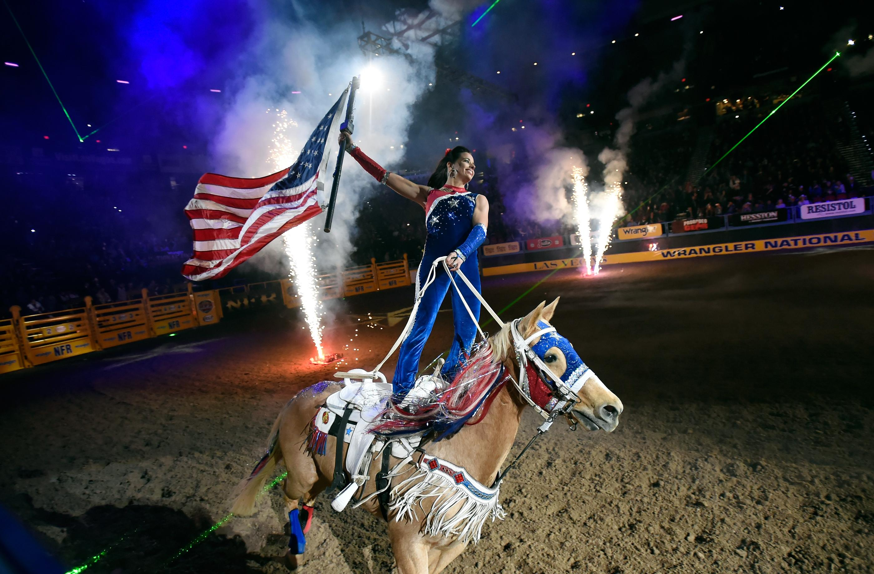 A rider carries the American flag during the opening ceremonies before the start of the seventh go-round of the National Finals Rodeo Wednesday, Dec. 13, 2017, in Las Vegas. CREDIT: David Becker/Las Vegas News Bureau