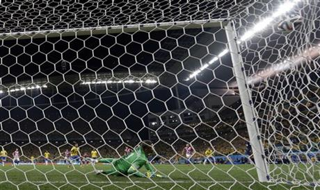 Croatia's goalkeeper Stipe Pletikosa deflects the ball as Brazil's Neymar scores his side's 2nd goal from the penalty spot during the group A World Cup soccer match between Brazil and Croatia.